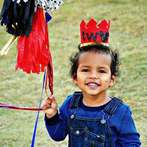 """Really cute two year old boy holding balloons with streamers and wearing a crown that says Two. The """"o"""" is a Mickey Mouse."""