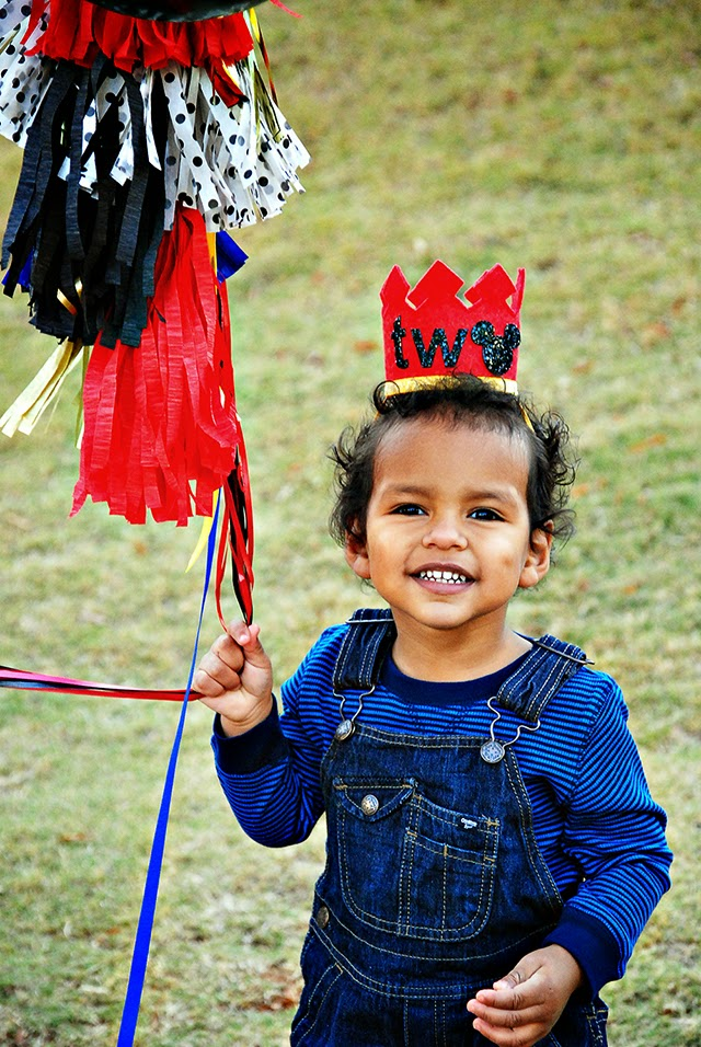 "Really cute two year old boy holding balloons with streamers and wearing a crown that says Two. The ""o"" is a Mickey Mouse."
