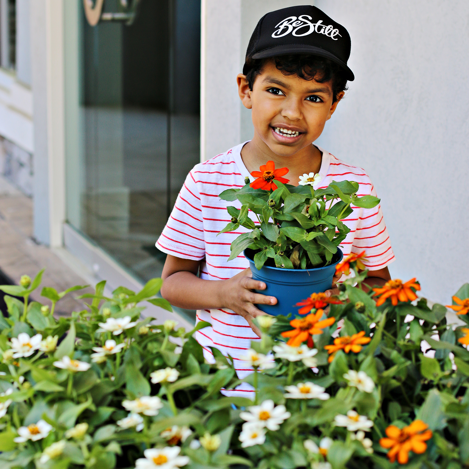 A boy stands behind a table of potted flowers, holding a pot of flowers. It's just one of the easy ways to make every day Earth Day with kids. He's spending time outdoors.
