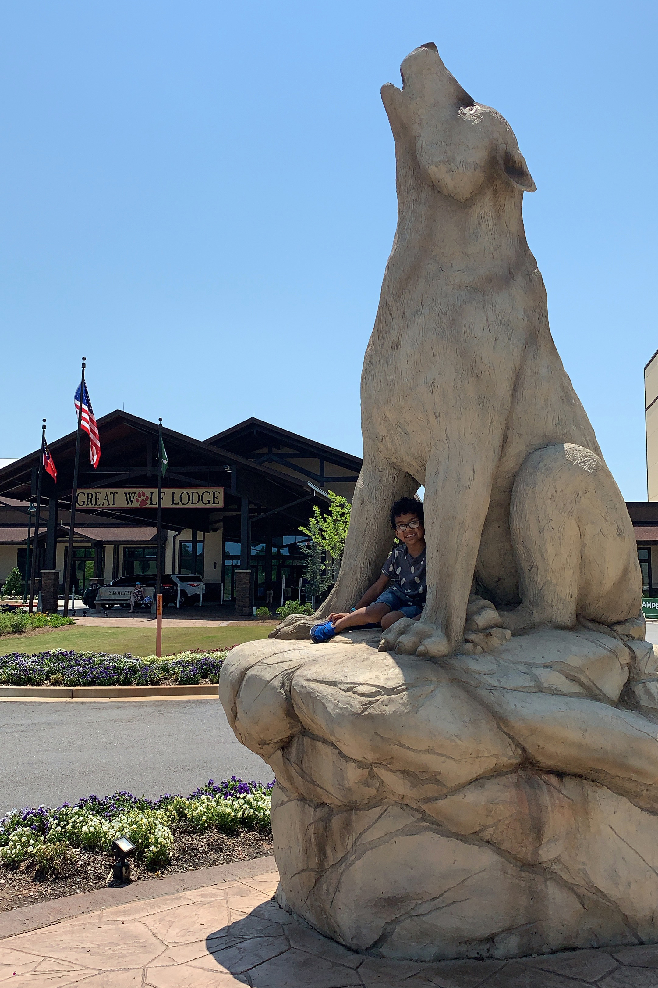 Great Wolf Lodge Kicks-off Summer Camp-IN: We Surprised Our Son with a Visit! Here is a photo of our son sitting on the giant wolf statue outside of Great Wolf Lodge in Atlanta / LaGrange, Georgia.