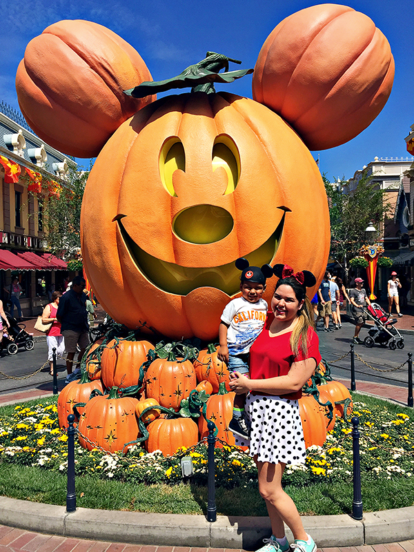 Mother and son standing in front of a giant Mickey Mouse pumpkin at Disneyland in California.