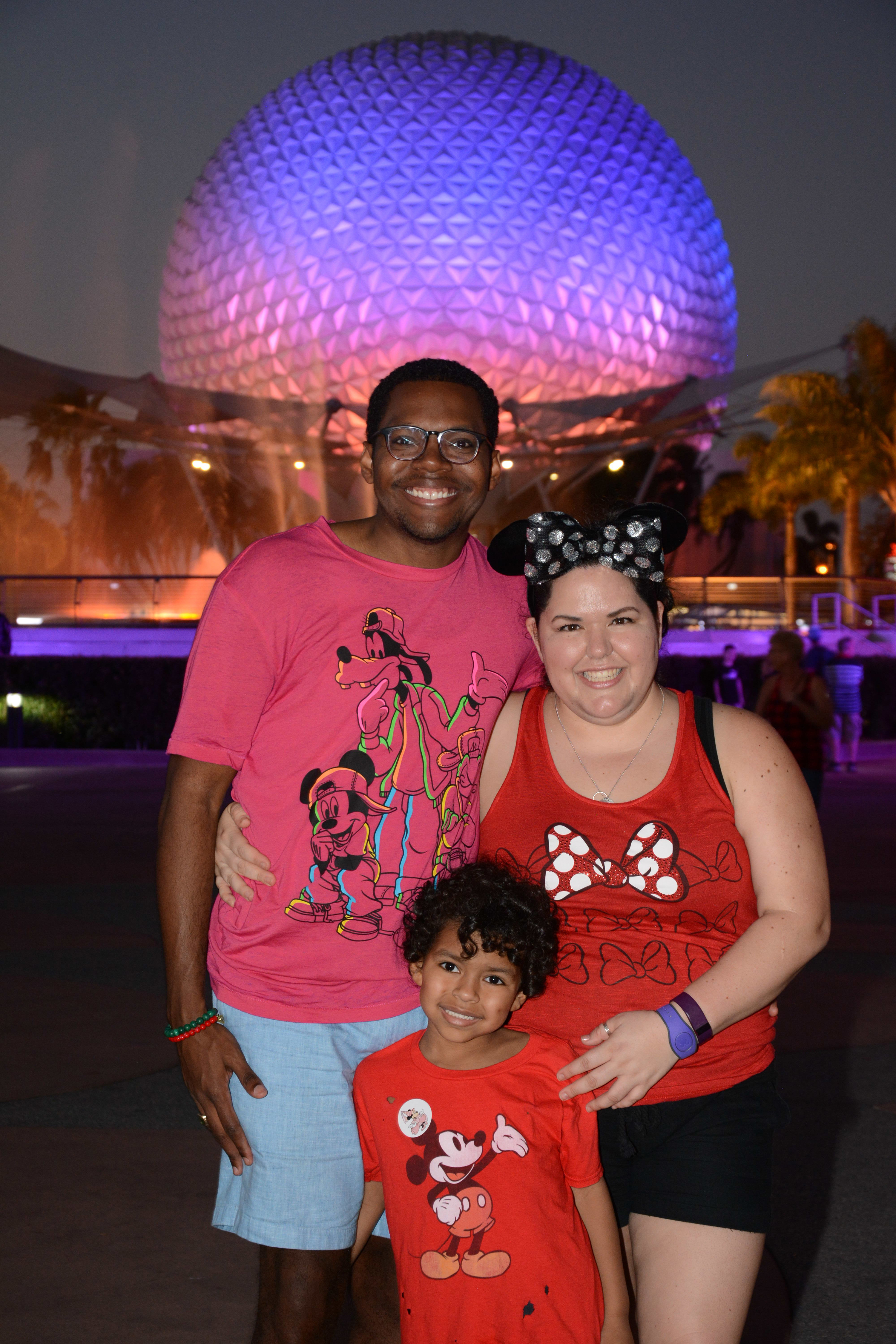Dad, Mom, and son standing in front of Epcot at night, in disney shirts.