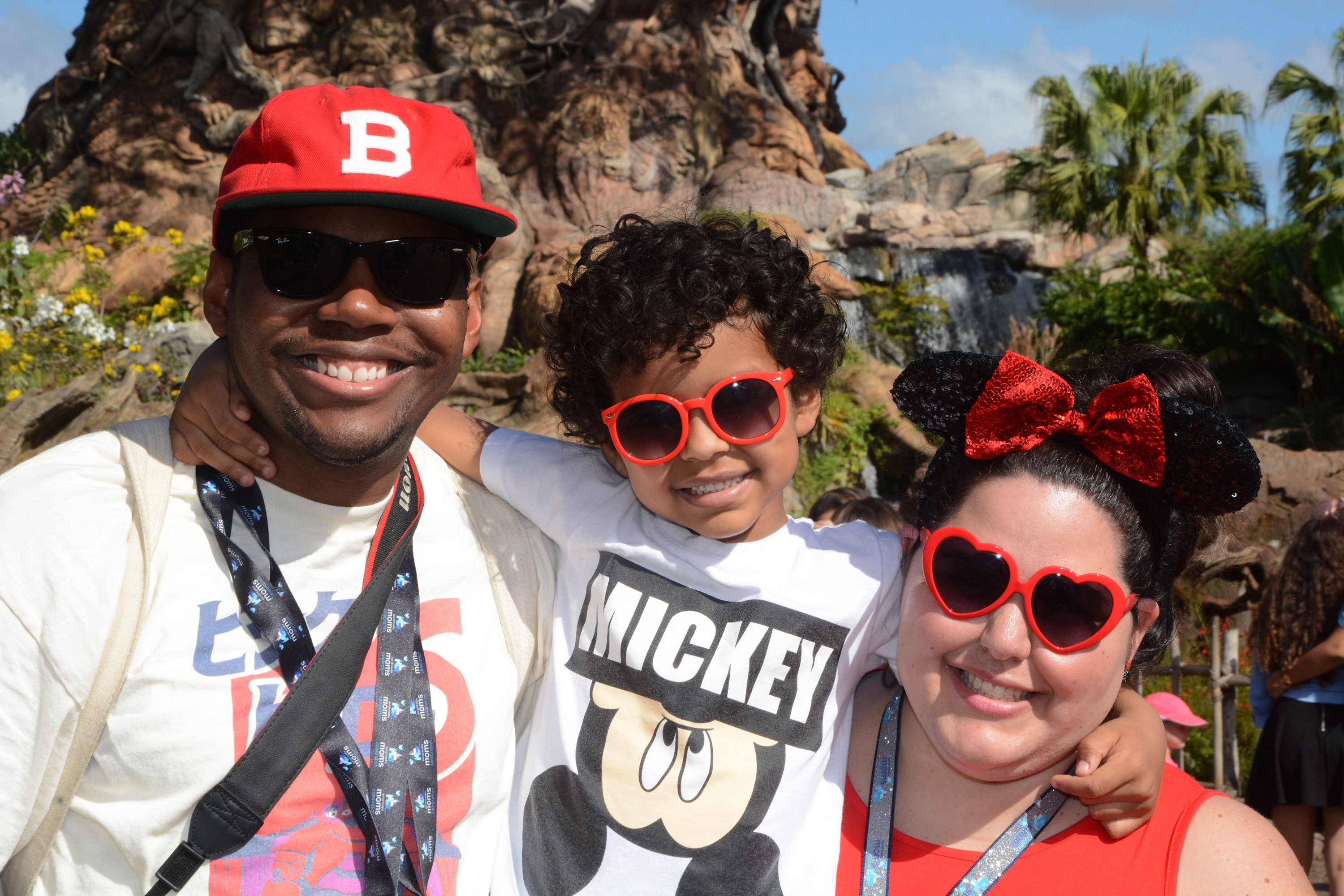 The Pete Family at Walt Disney World Animal Kingdom. Dad, child, and mom smiling in sunglasses in front of a waterfall.