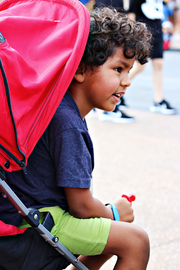 Boy at Walt Disney World sitting in a stroller.