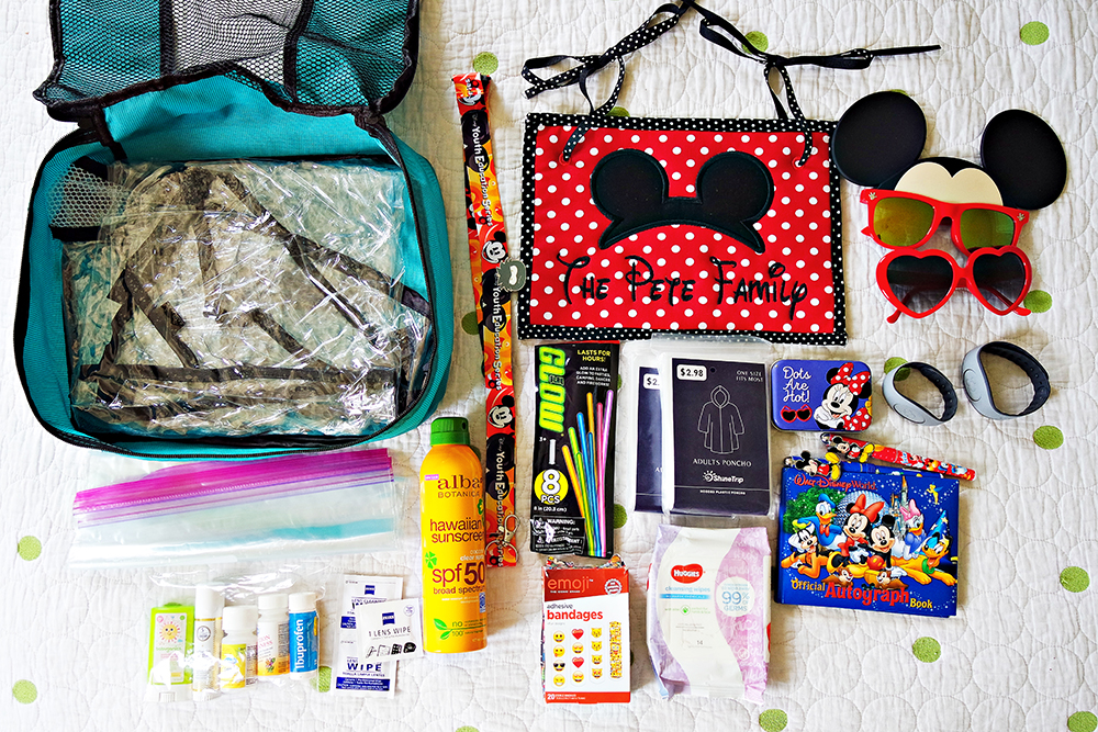 The ultimate emergency bag for Disney to store under your stroller, laid out in a flat lay. It's a packing cube bag, ponchos, medicine, sunglasses, an autograph book and pens, technology wipes, bandaids, Disney pins and lanyard, extra magic bands, glow sticks, wipes, sunscreen, and stroller cover in case of rain.