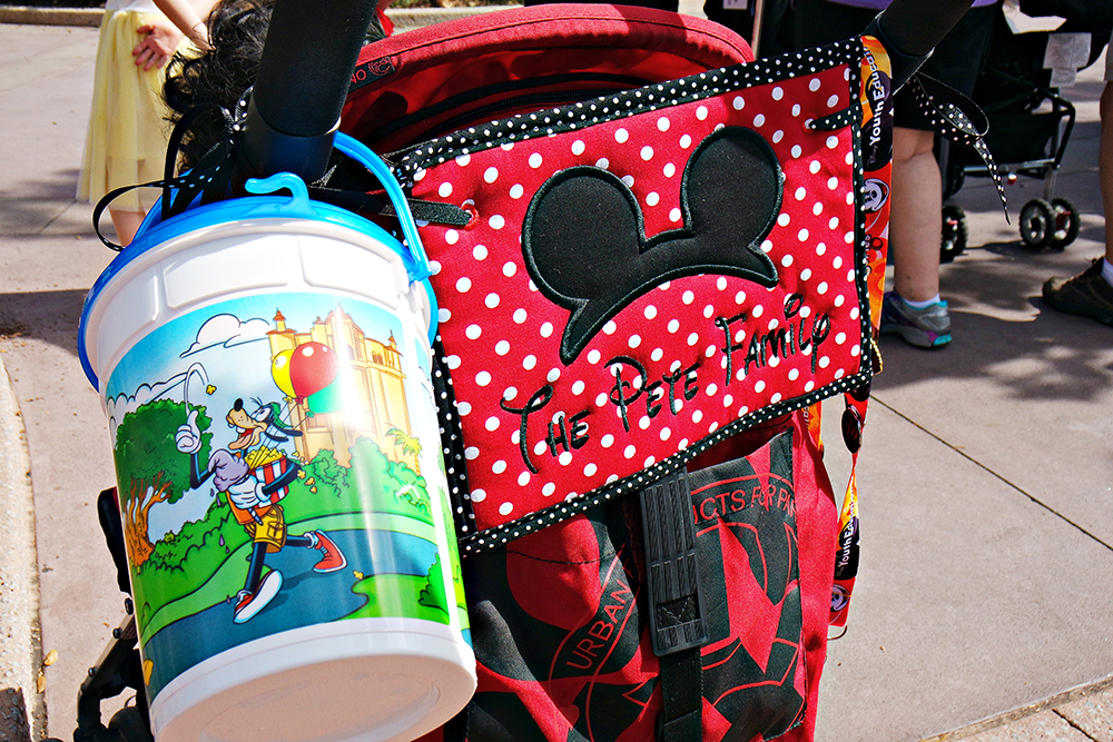 A photo of our stroller at the Disney parks. Shows a stroller spotter sign that says The Pete Family and a Disney popcorn bucket.