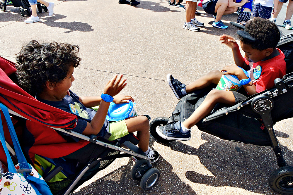 Two kids in their strollers at Disney, with Disney popcorn buckets.