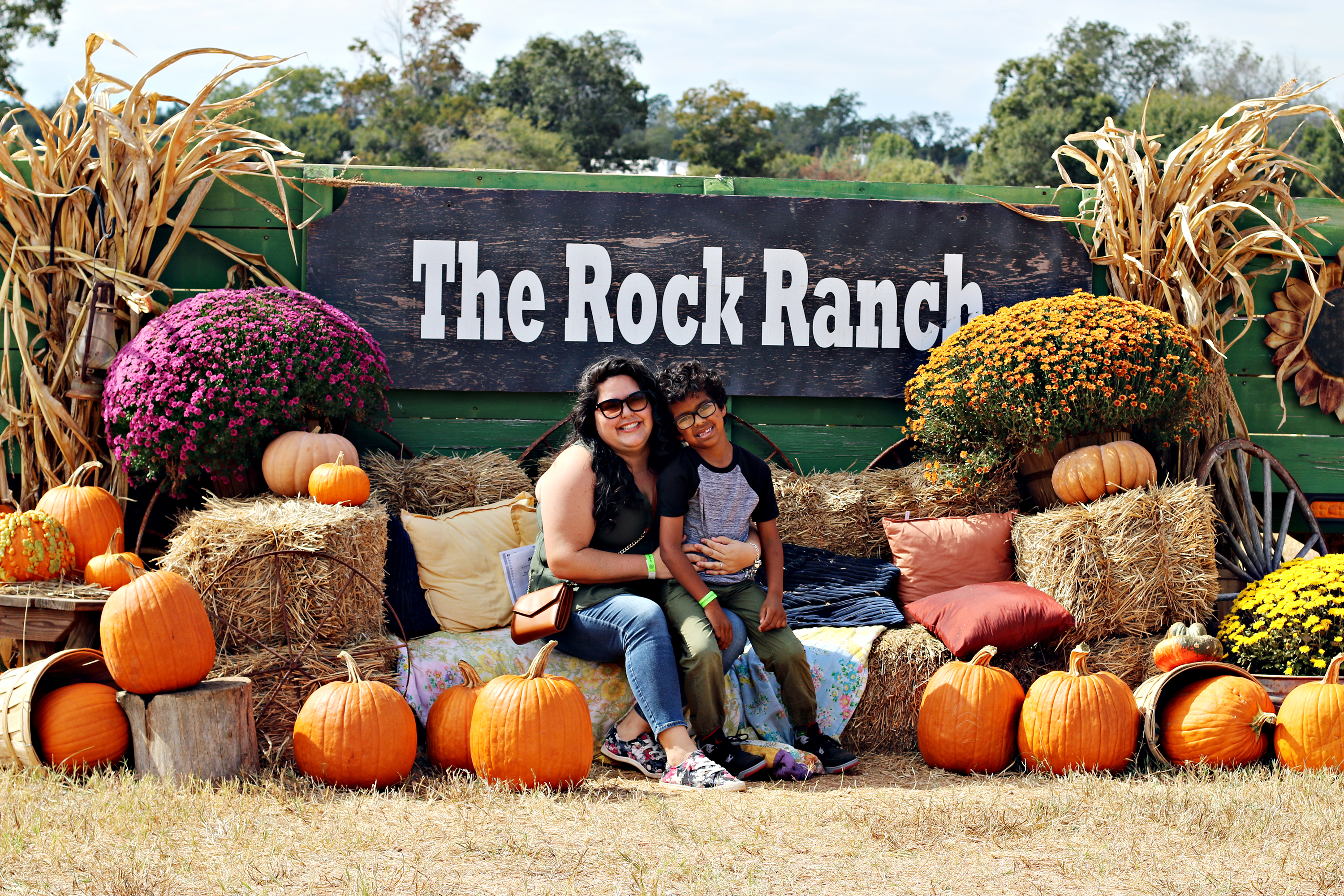 Mom and son sitting on hay, surrounded by pumpkins and mums, under a sign that says The Rock Ranch.