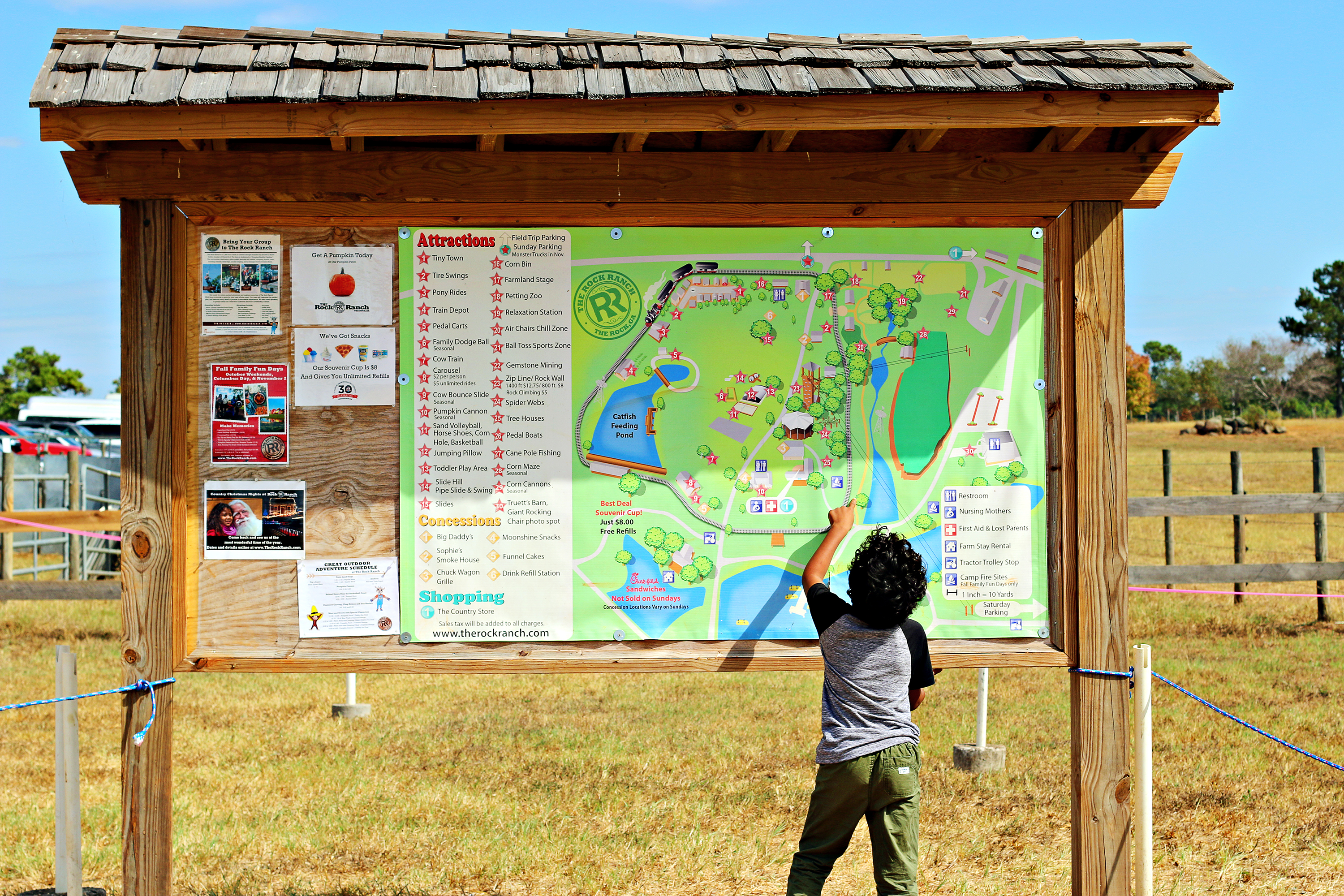 Boy pointing to an attraction on The Rock Ranch map.