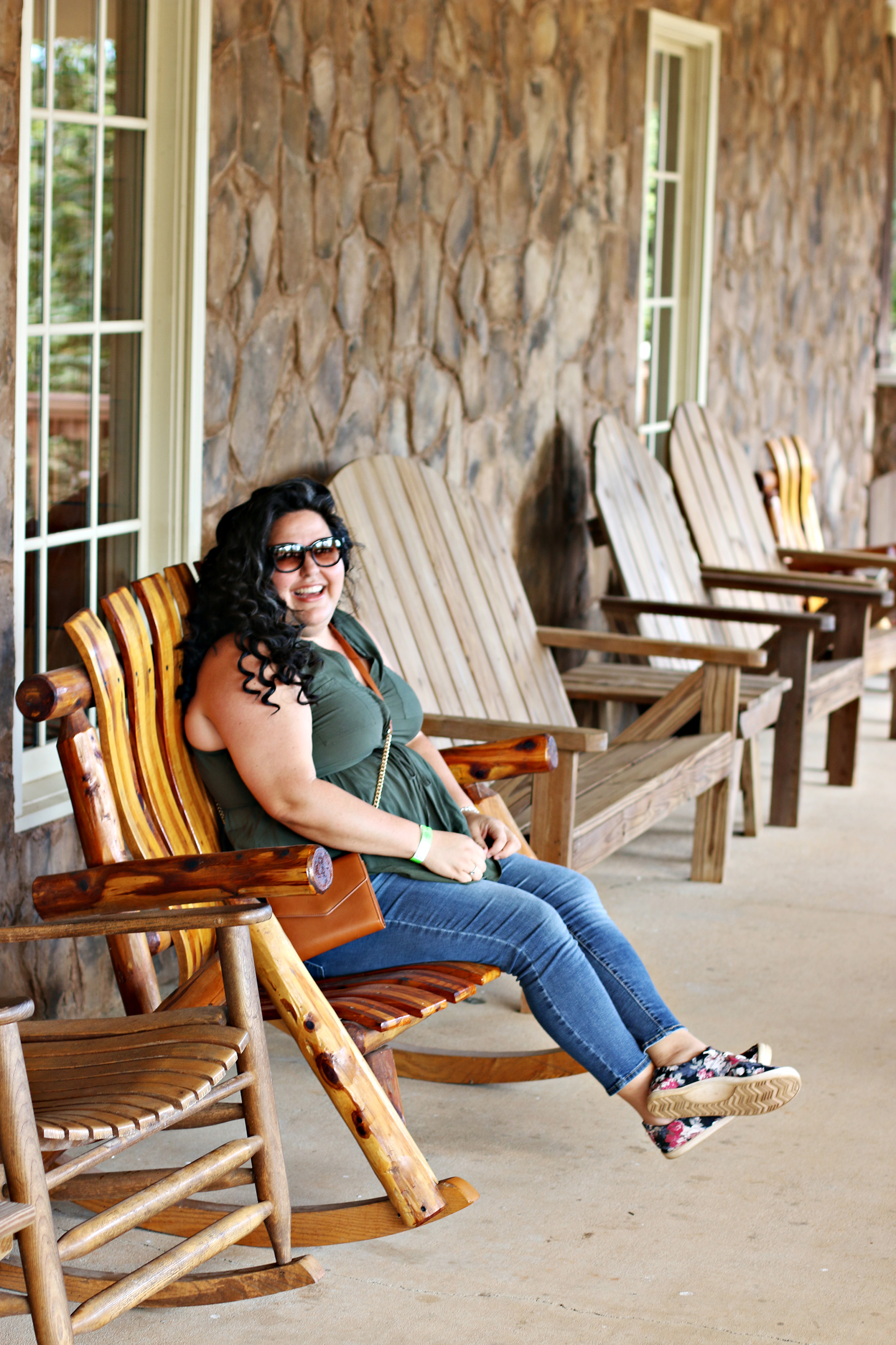 Woman smiling and rocking in a rocking chair at The Rock Ranch.