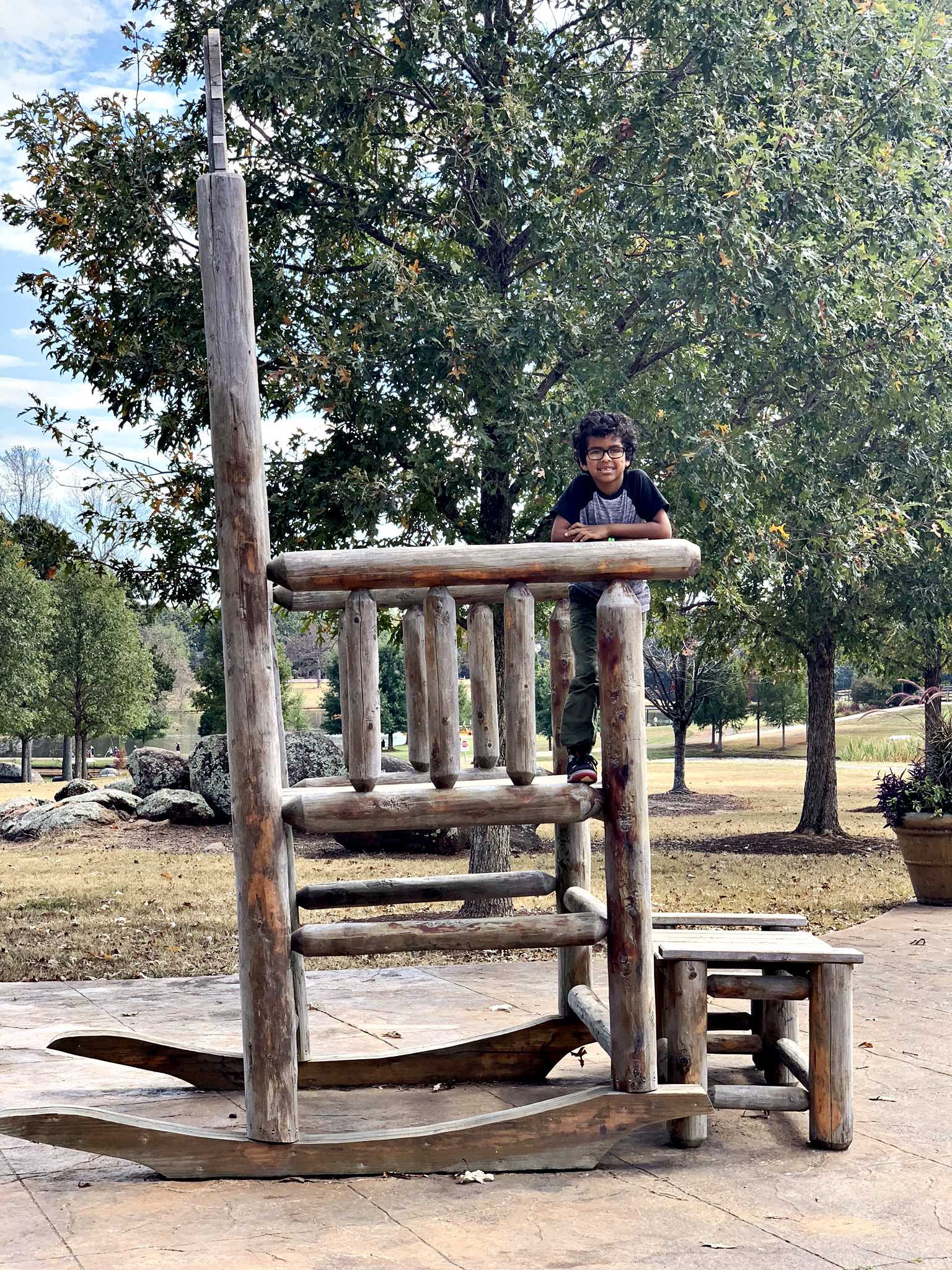 Boy standing on a giant rocking chair at The Rock Ranch.