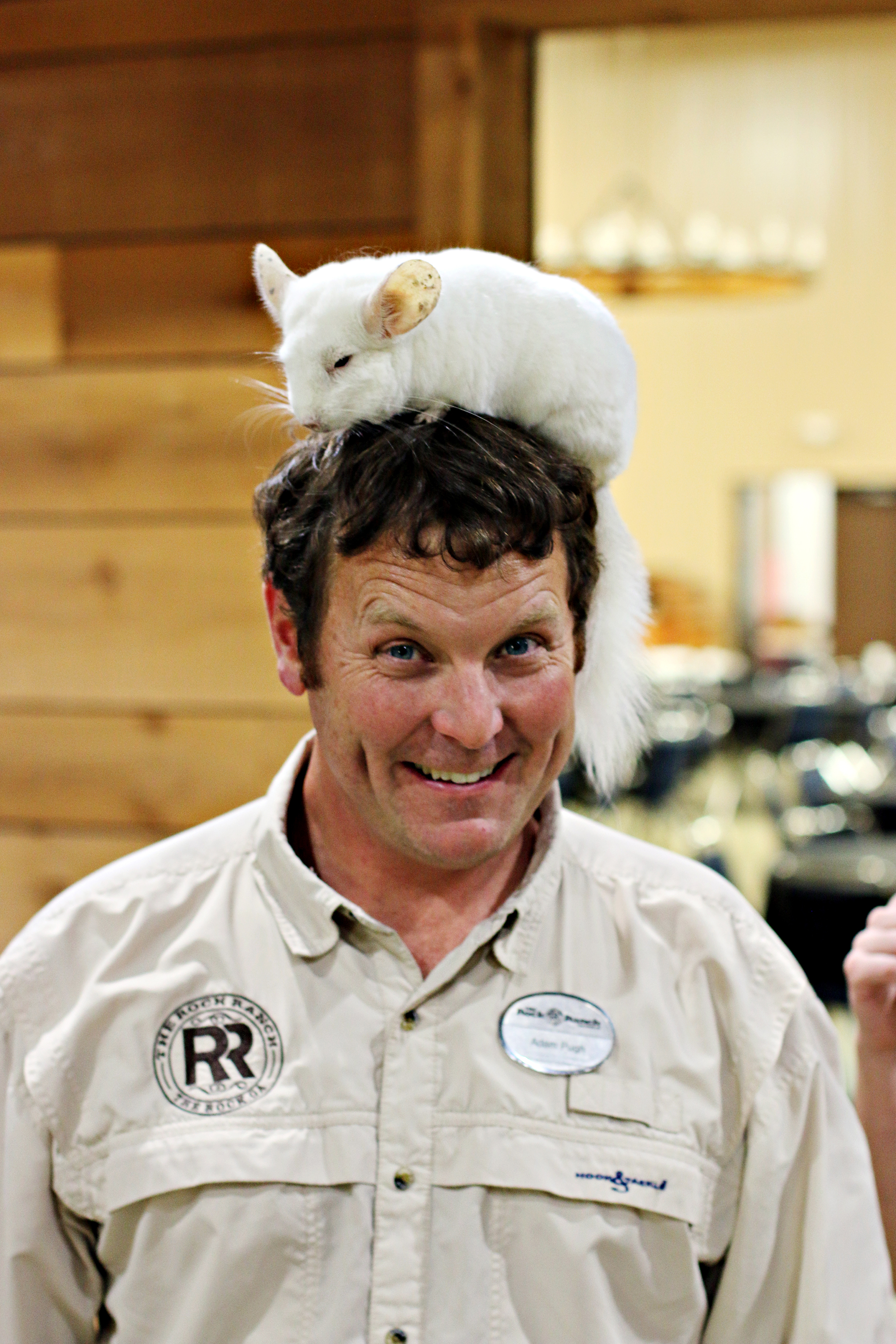 Smiling employee of The Rock Ranch with a chinchilla on his head.