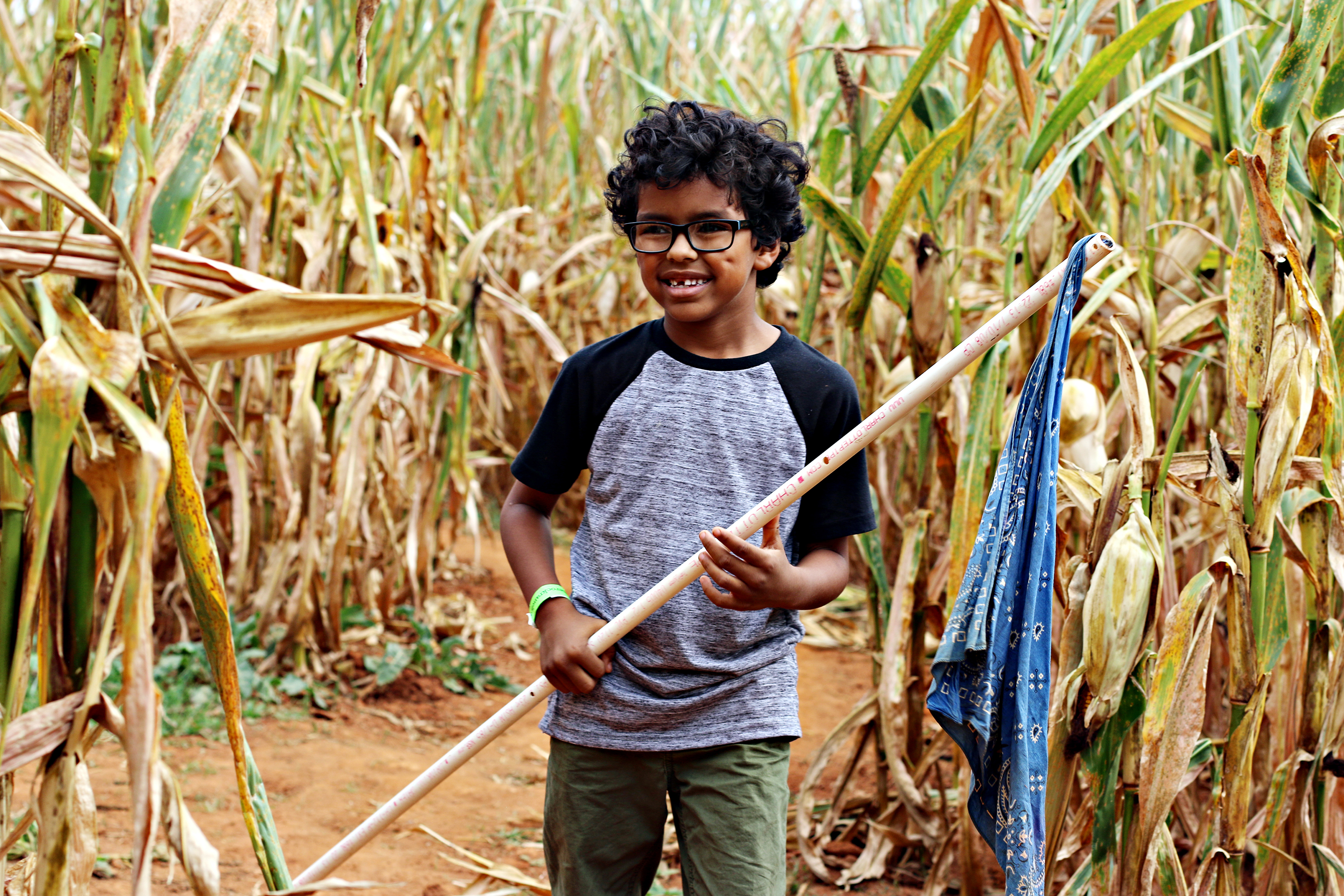 Smiling boy holding a flag in the corn maze at The Rock Ranch.