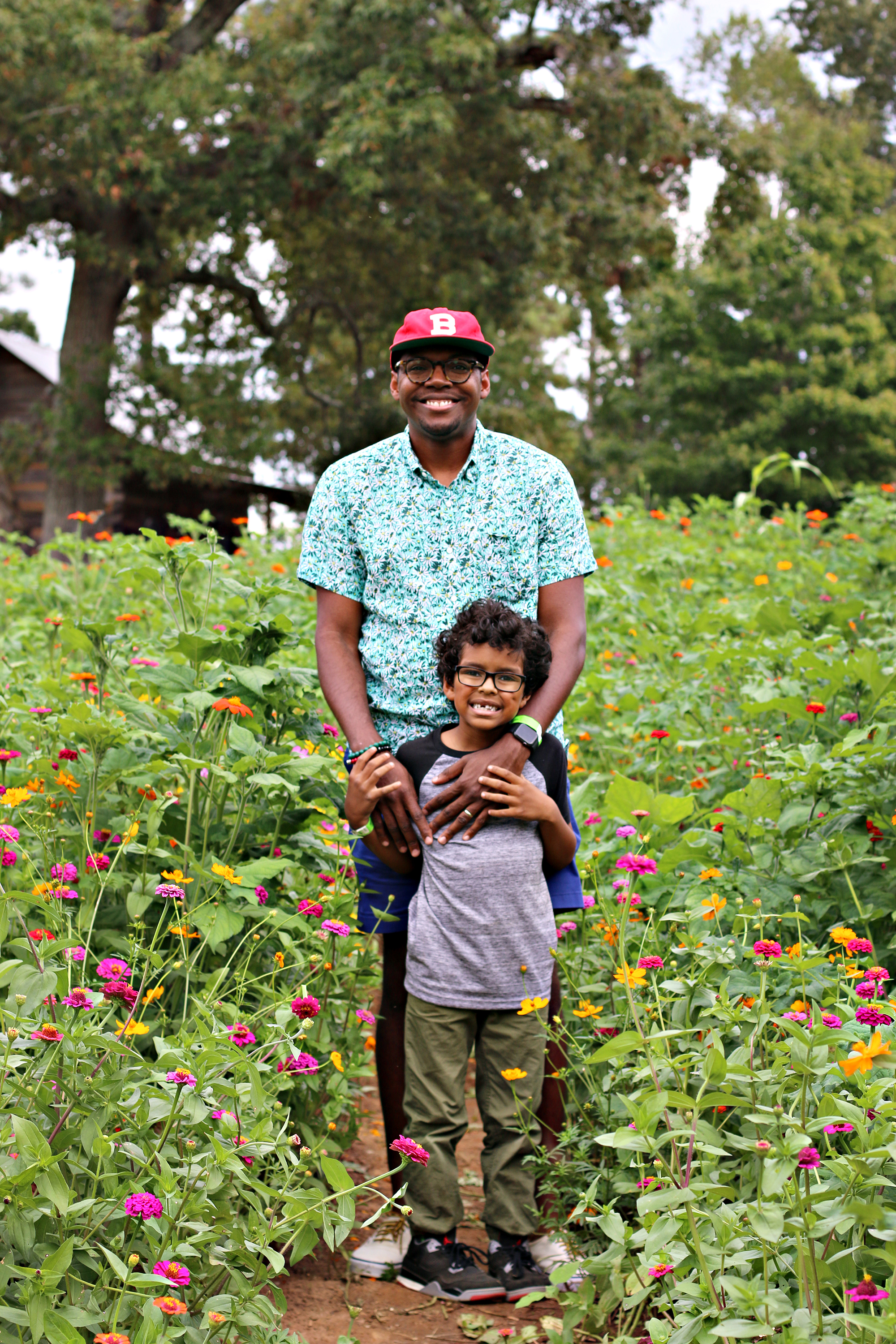 Dad and son smiling and posing in a flower garden at The Rock Ranch.
