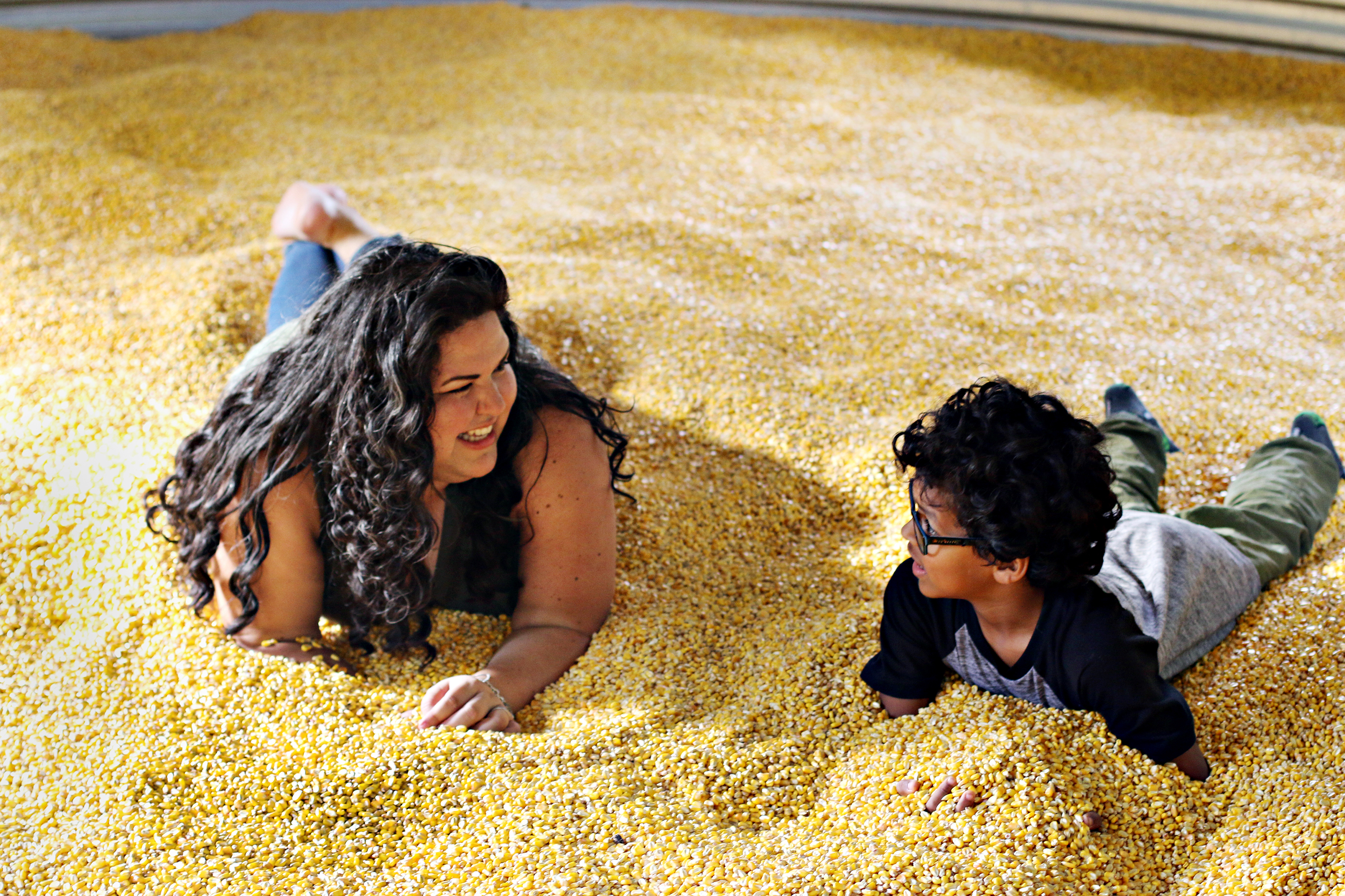 Mom and son looking at each other and smiling in the corn pit at The Rock Ranch.
