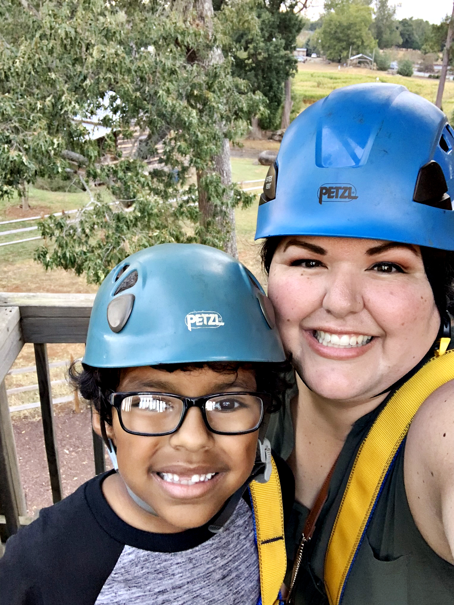 Smiling mom and son in zip line gear, ready to go down the Cow-a-bunga! zip line at The Rock Ranch.