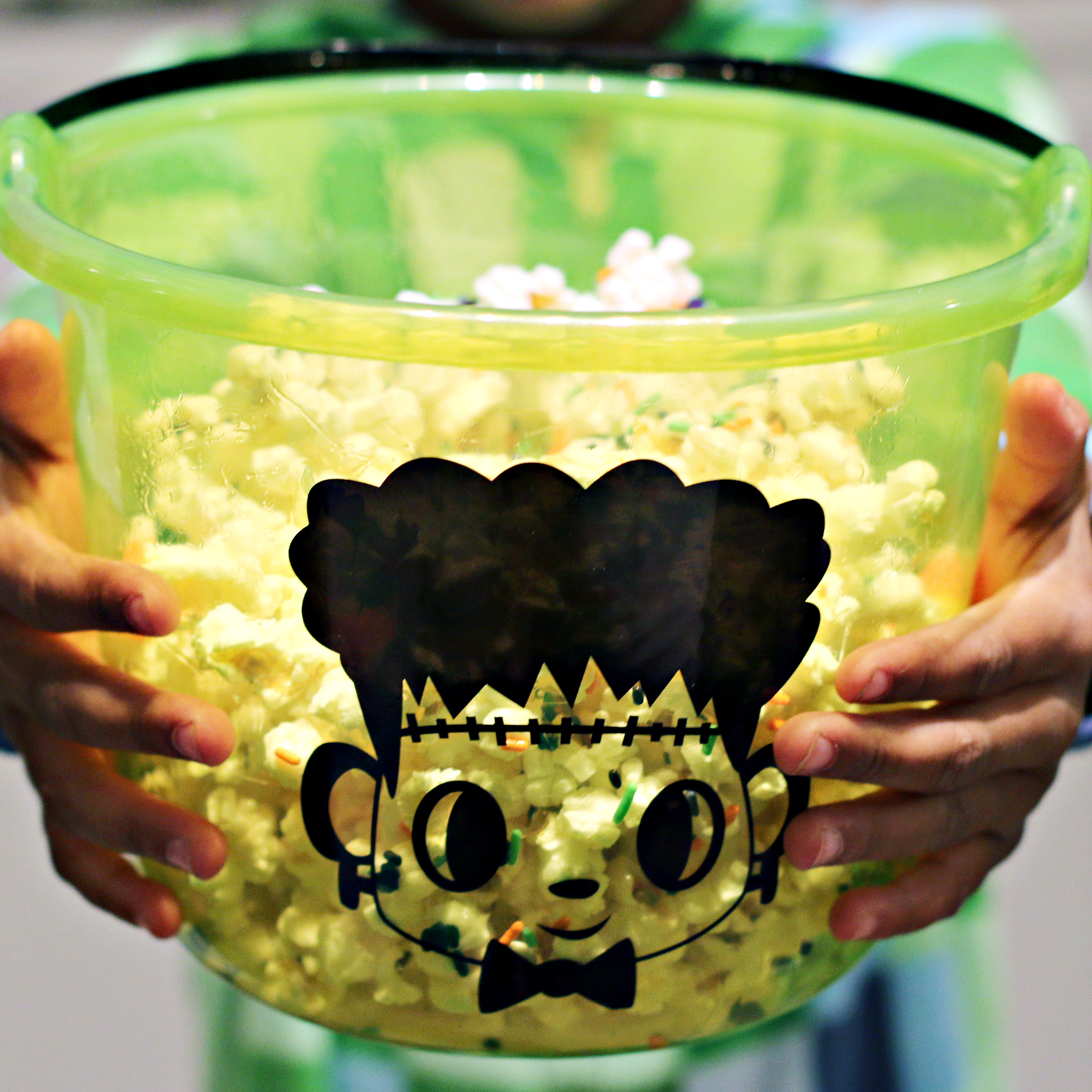 Child holding a Halloween bucket with Frankenstein on it Filled with Monster Mash popcorn treat.