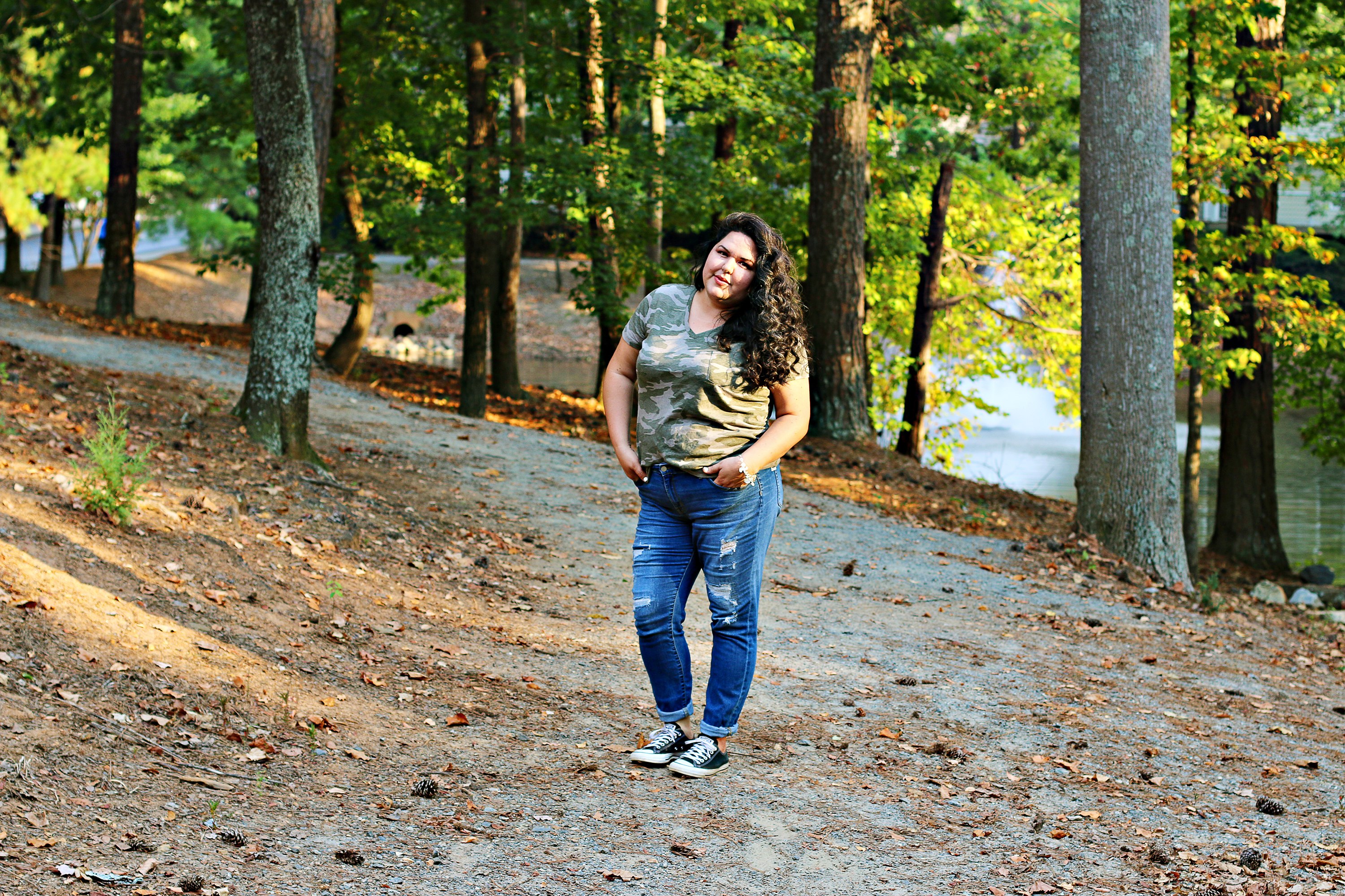 Woman with curly hair standing in front of a lake. She's wearing denim jeans and a camo print tee and a custom charm bracelet from James Avery Artisan Jewelry.