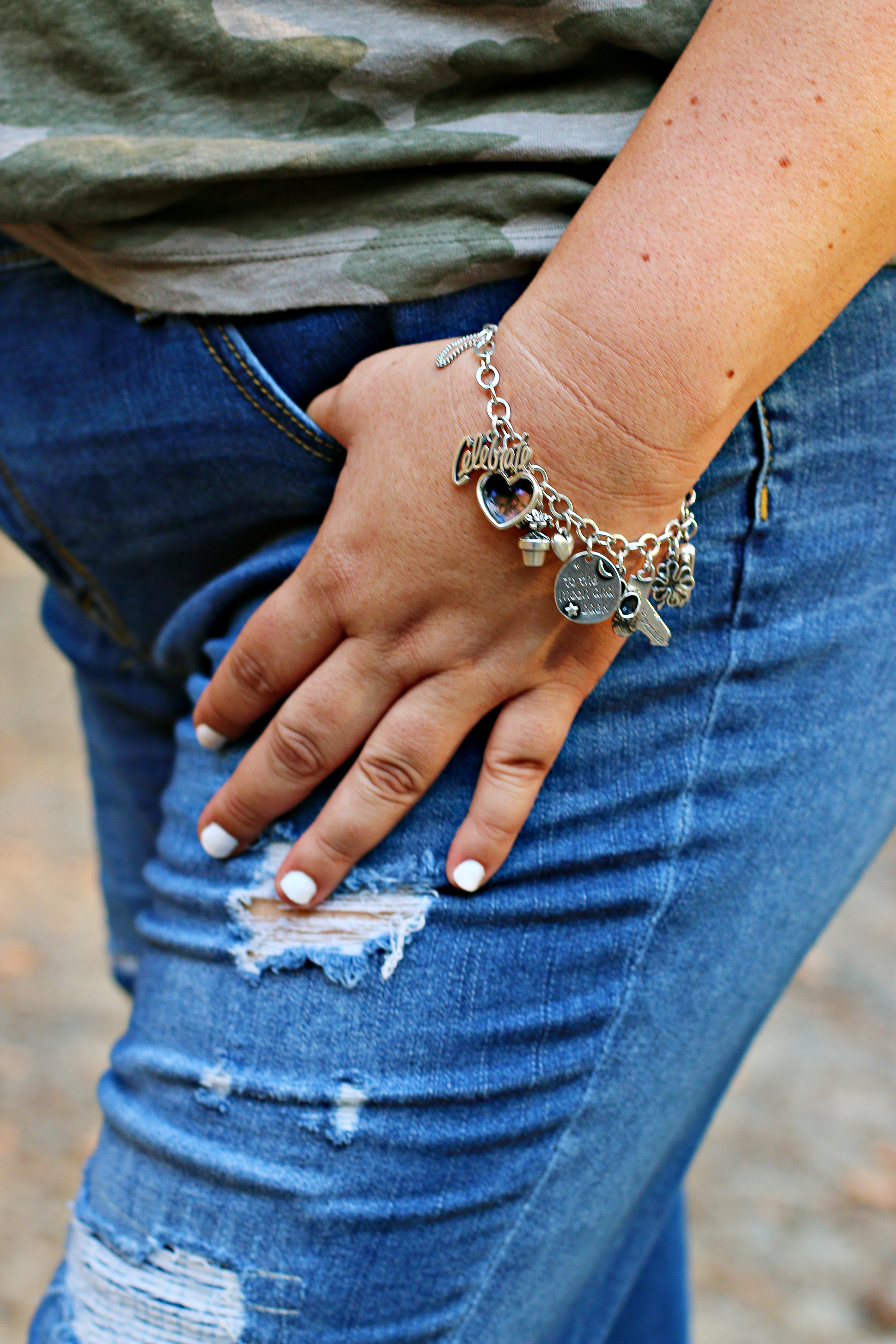 A close up of a woman showing her custom charm bracelet from James Avery Artisan Jewelry.