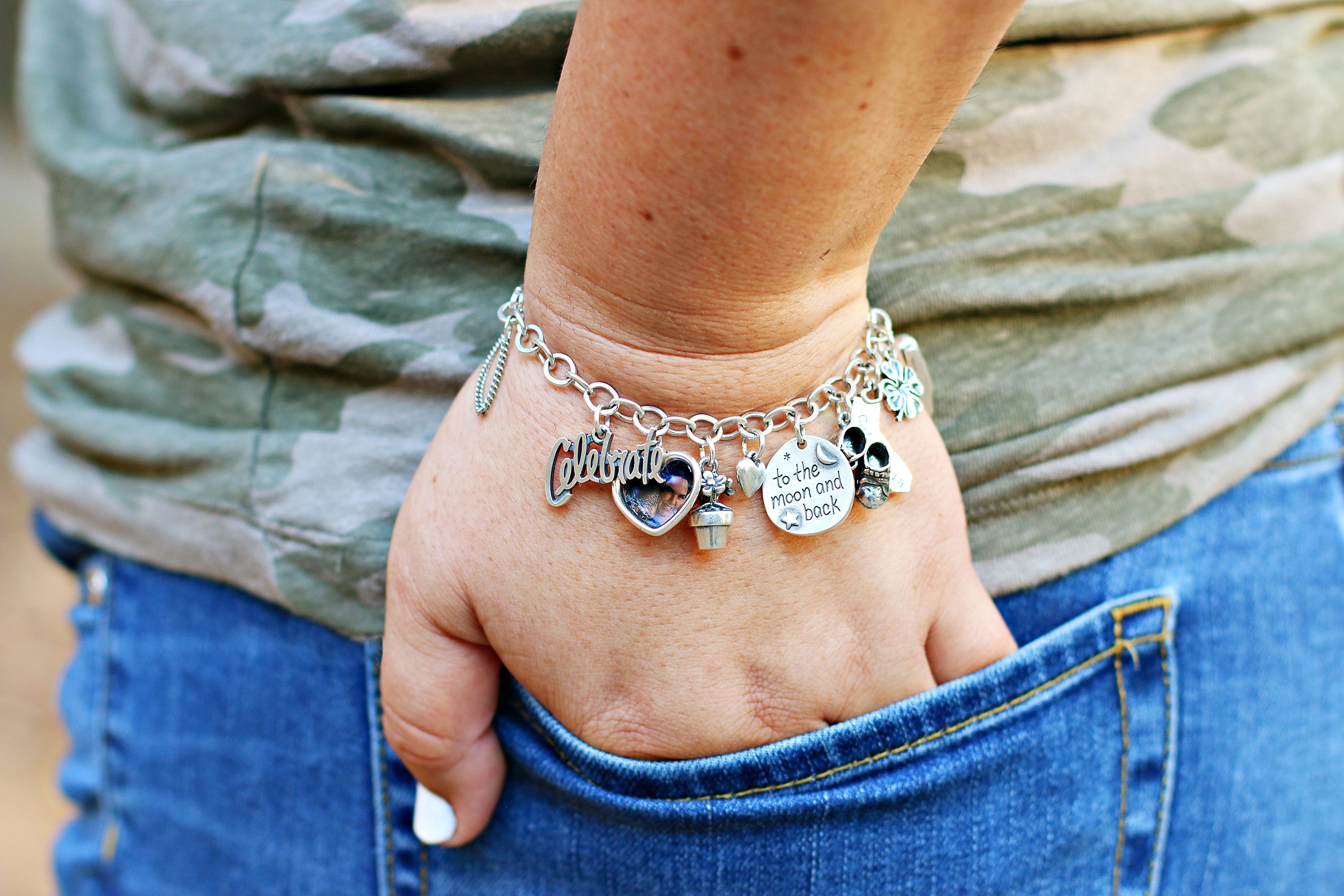 """A custom charm bracelet from James Avery Artisan Jewelry. One charm says Celebrate. There is a heart picture frame charm, a potted flower charm, a small heart charm, a charm that says """"to the moon and back"""", baby shoes, a charm of California, a shamrock charm, and cruise ship charm."""