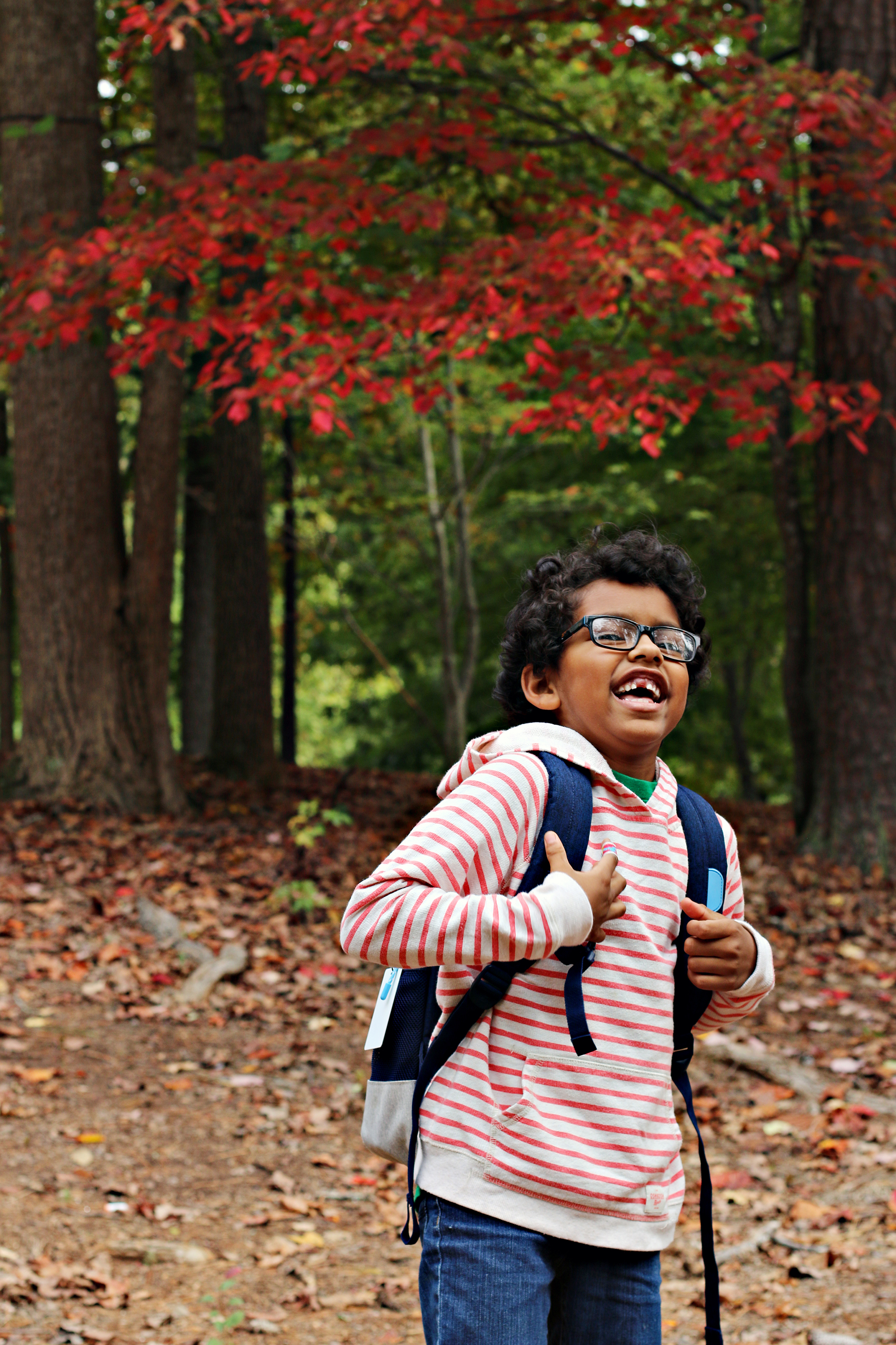Laughing boy in front of a red tree, holding his backpack.