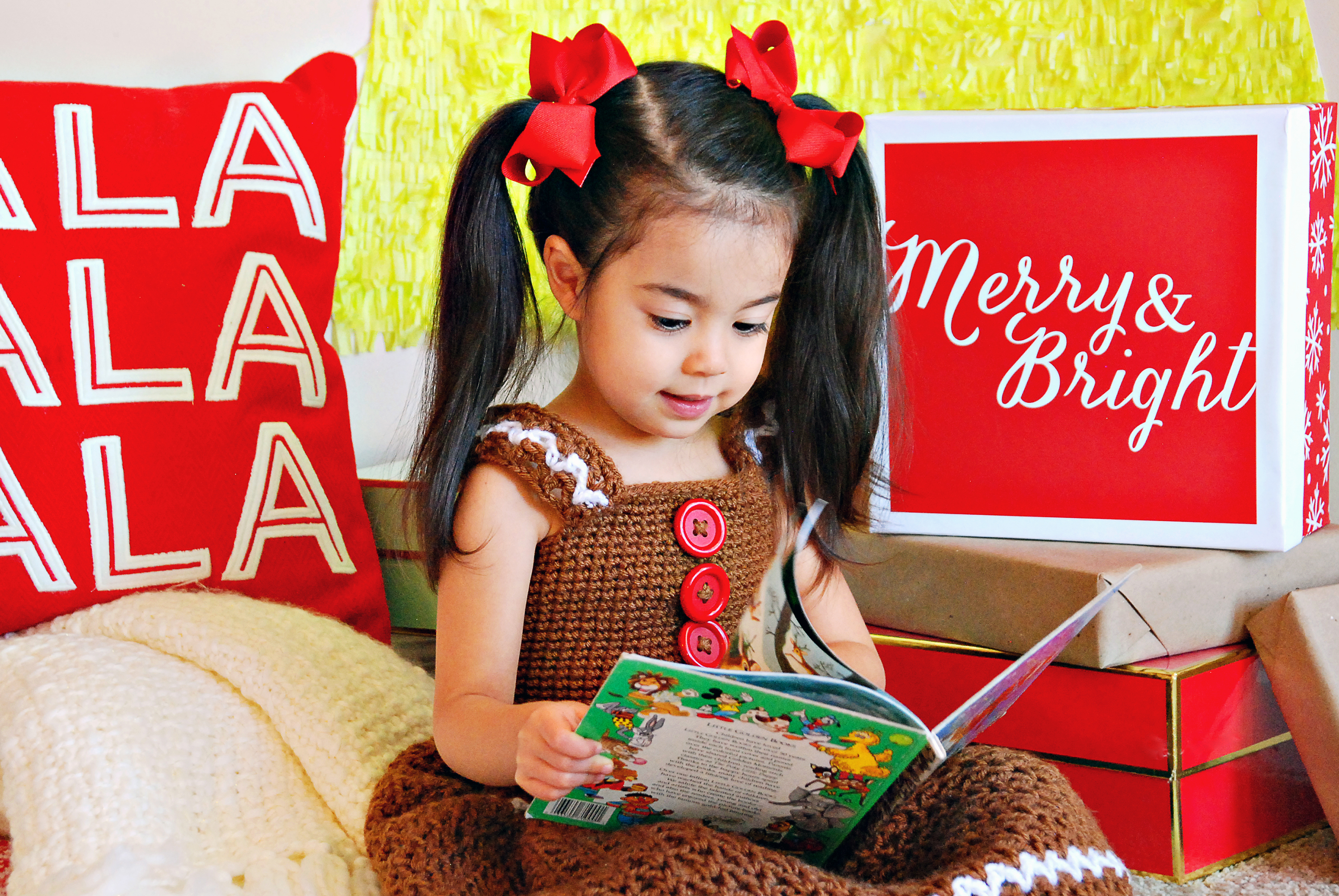 A girl sitting in a Christmas studio setting, reading a children's book.