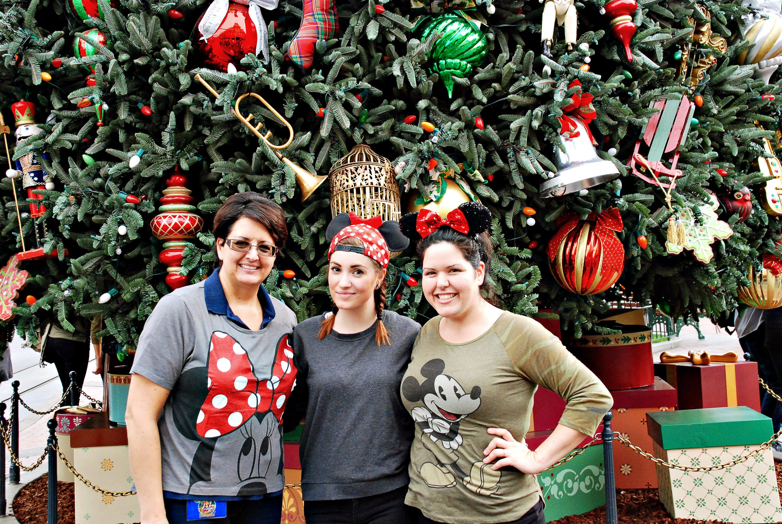 Mom and adult daughters standing in front of the Christmas tree on Main Street at Disneyland.