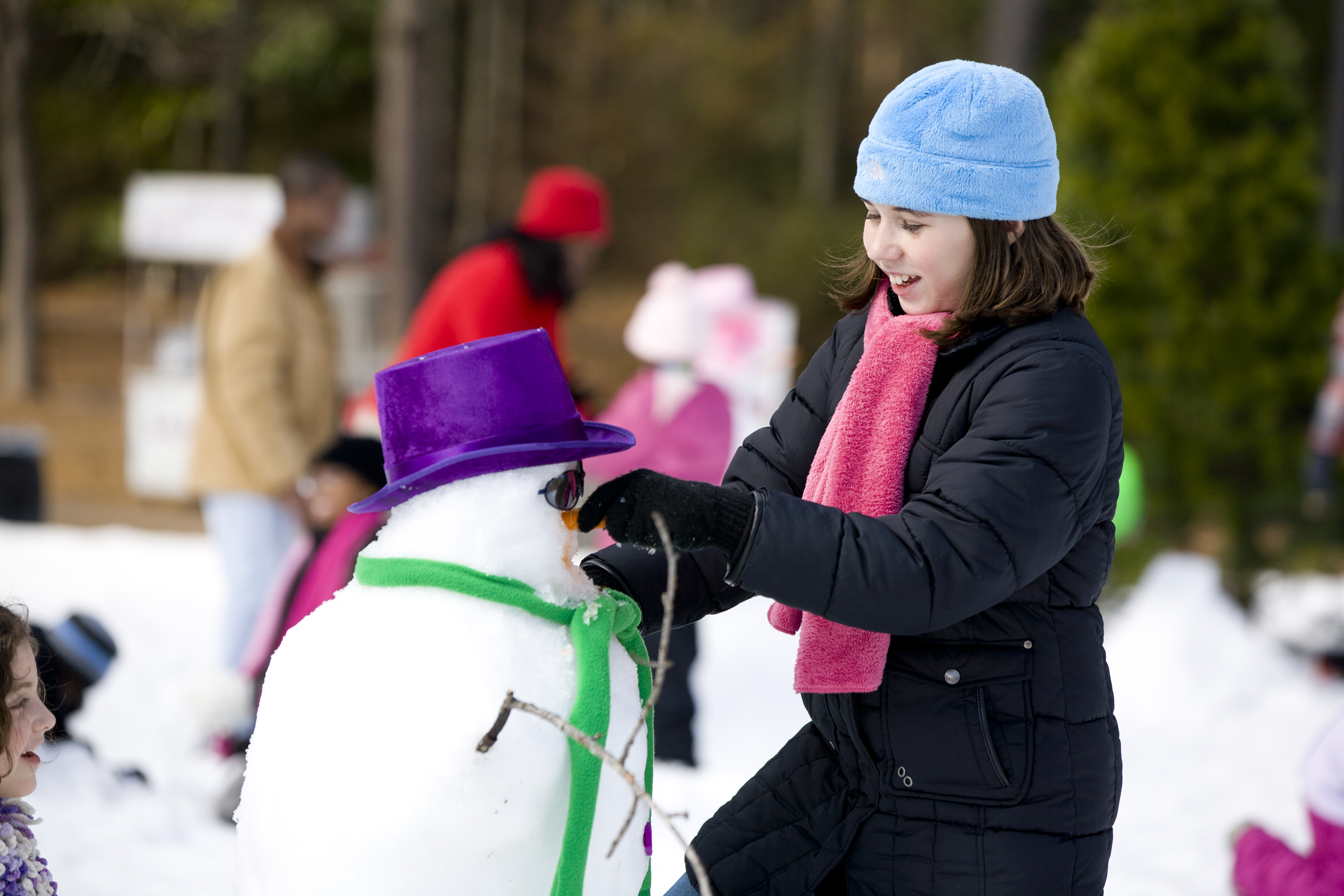 Girl building a snowman at Snow Mountain at Stone Mountain Park.