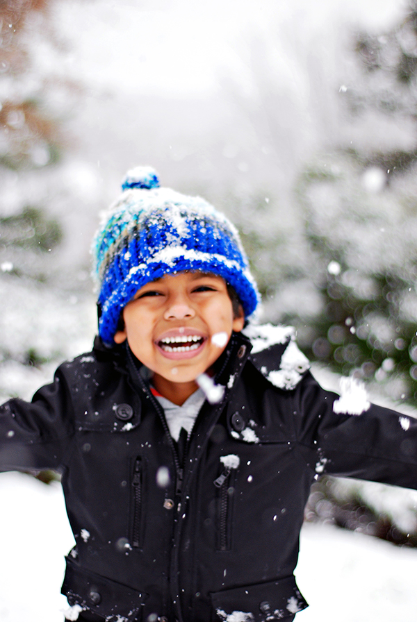 Snow day in Atlanta! This is a happy boy smiling and holding out his arms in the snow.