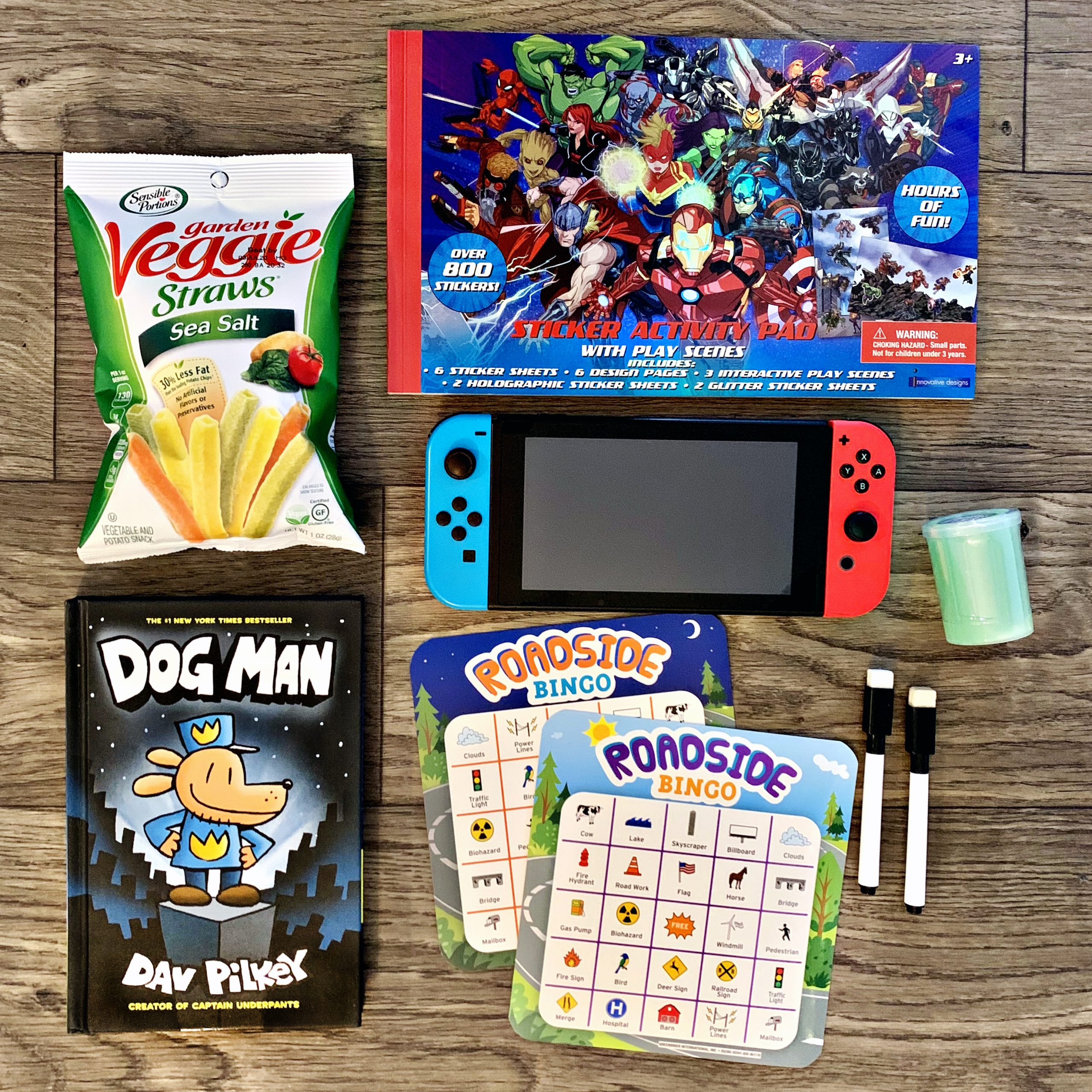 Items for traveling with big kids. Photo includes a personal bag of Sensible Portions® Garden Veggie Straws, a Marvel-themed Sticker activity pad, a Nintendo Switch, a Dog Man book, glow-in-the-dark slime, and Roadside Bingo activity.