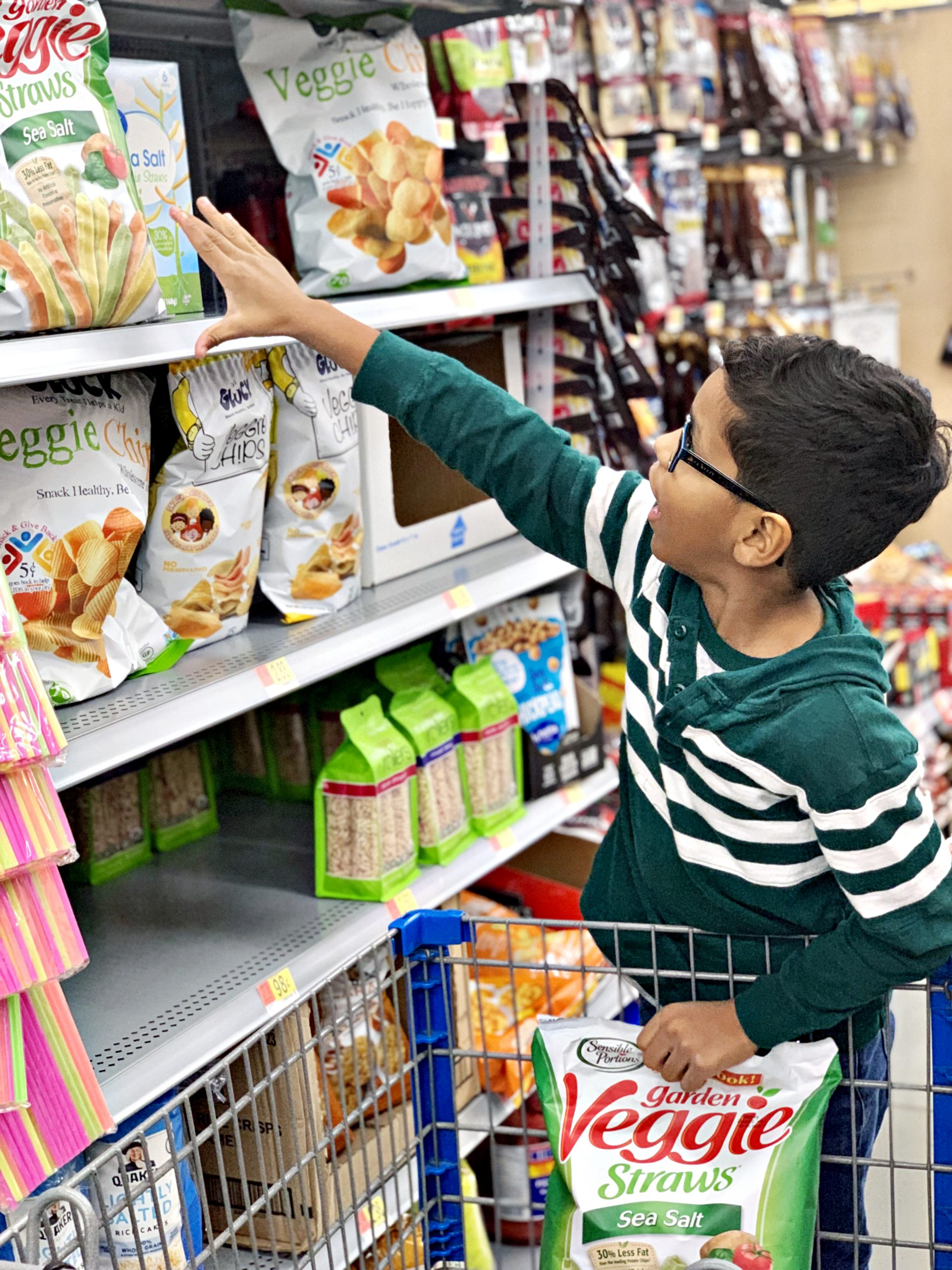 Boy reaching up for Sensible Portions® Garden Veggie Straws on the shelf at Walmart, while standing on a grocery cart, holding another bag.