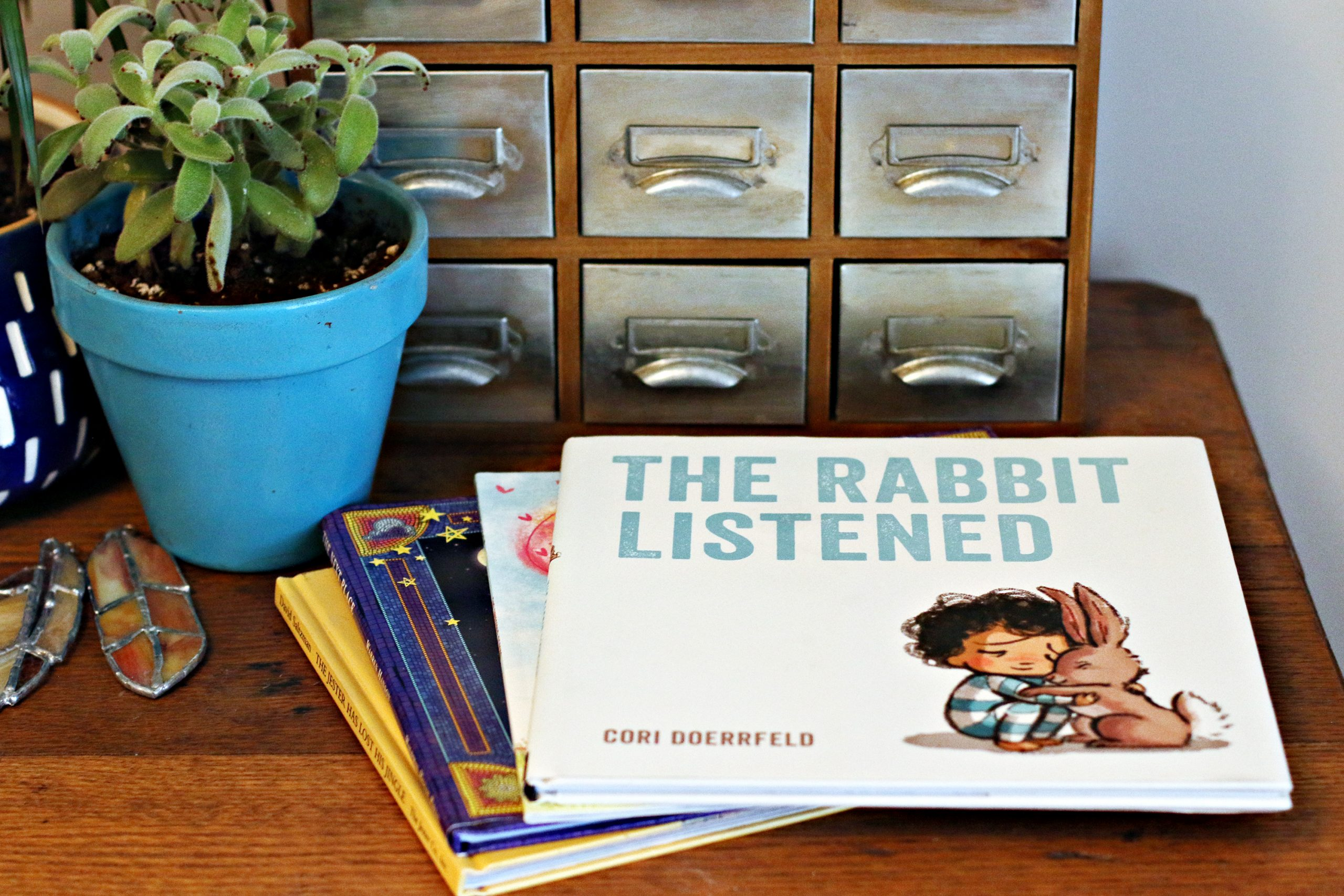 "A stack of children's books to help a grieving child. The top books is ""The Rabbit Listened"", by Cori Doerrfeld. The stack is on a table with a plant, display boxes, and stained glass feathers."