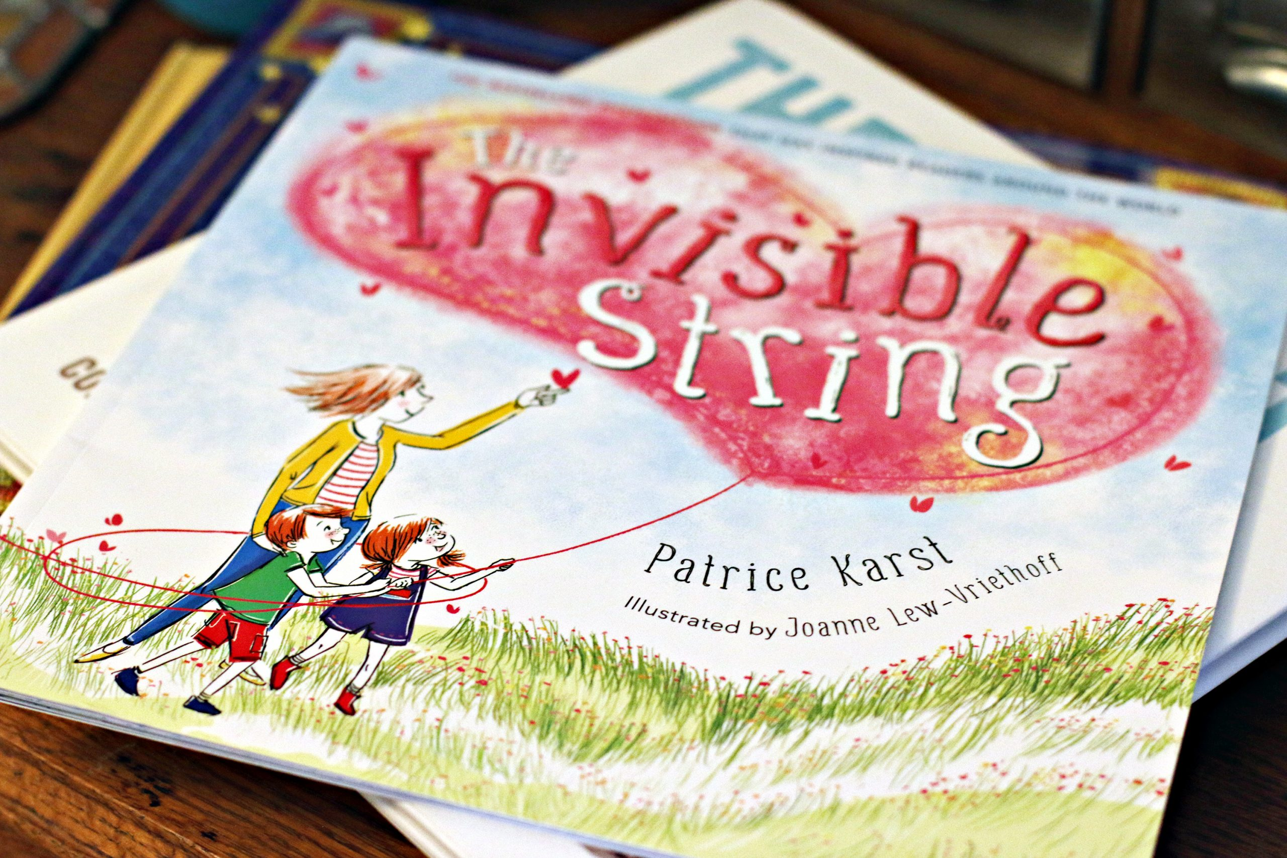 A close-up of the children's book, The Invisible String, by Patrice Karst, sitting on a stack of other books.