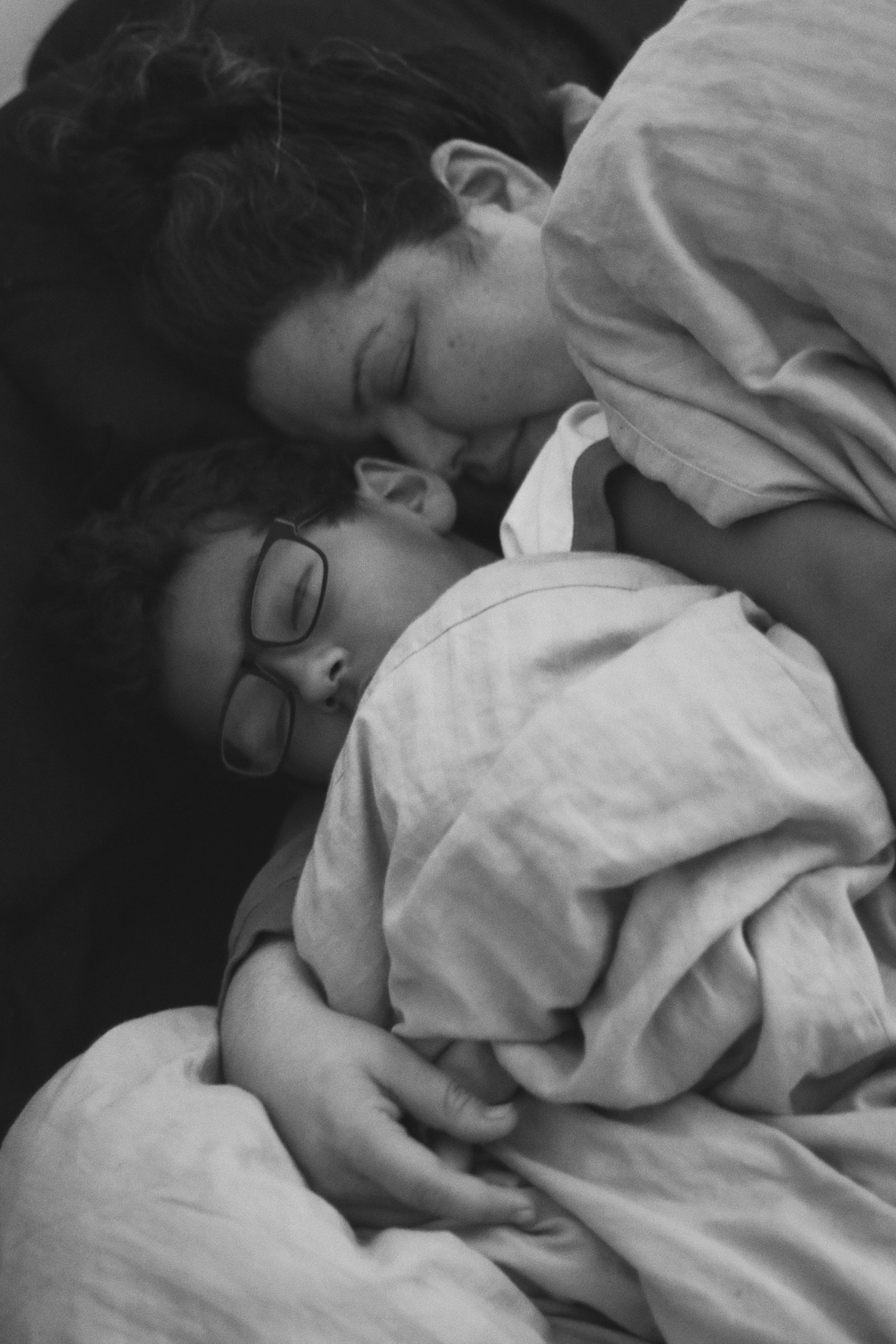 A mom and son, snuggling together, with their eyes closed.