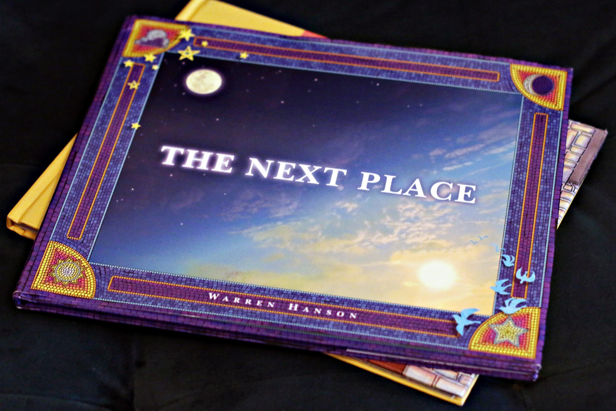 "A hardcover children's book called ""The Next Place"", by Warren Hanson, sitting on another book."