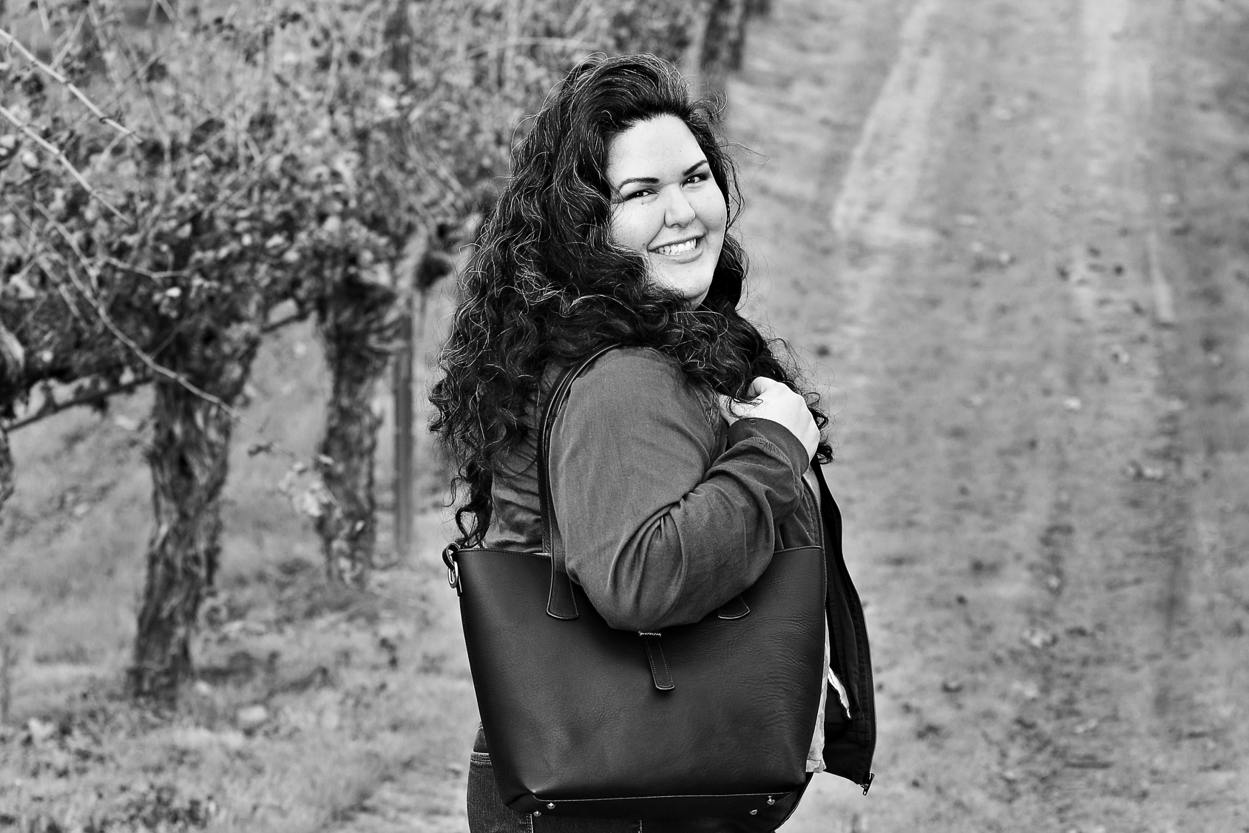 Black and white photo of a woman in a winery, holding a leather purse, and smiling big.