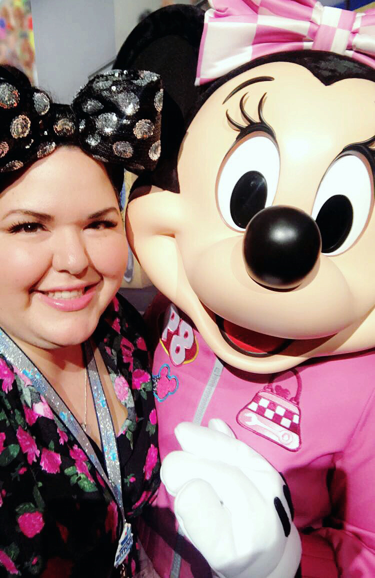 Woman posing with Minnie Mouse, wearing Minnie ears with a giant, sparking bow.