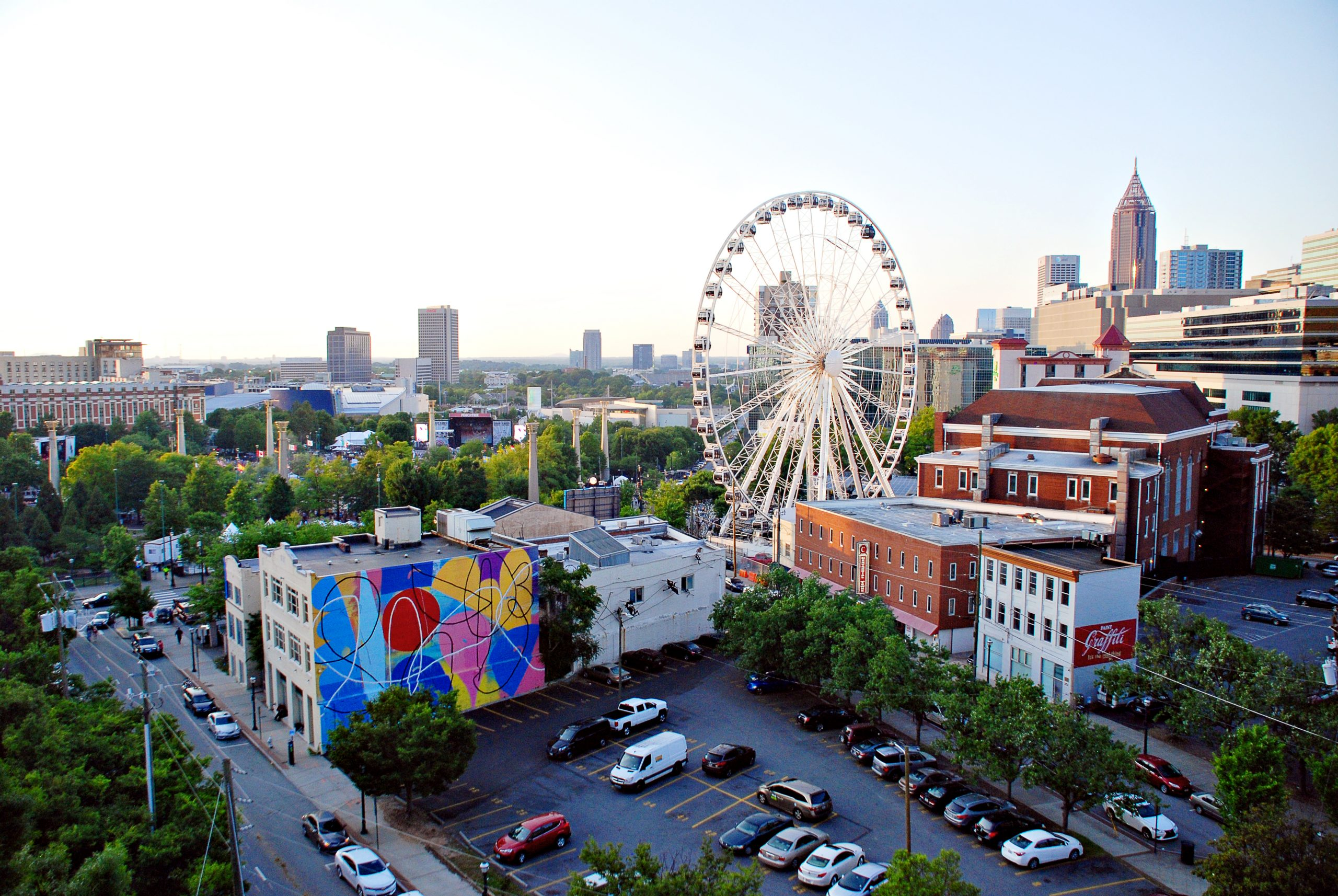 A view of Downtown Atlanta, that includes Centennial Olympic Park, SkyView Atlanta Ferris wheel, and Atlanta street art.