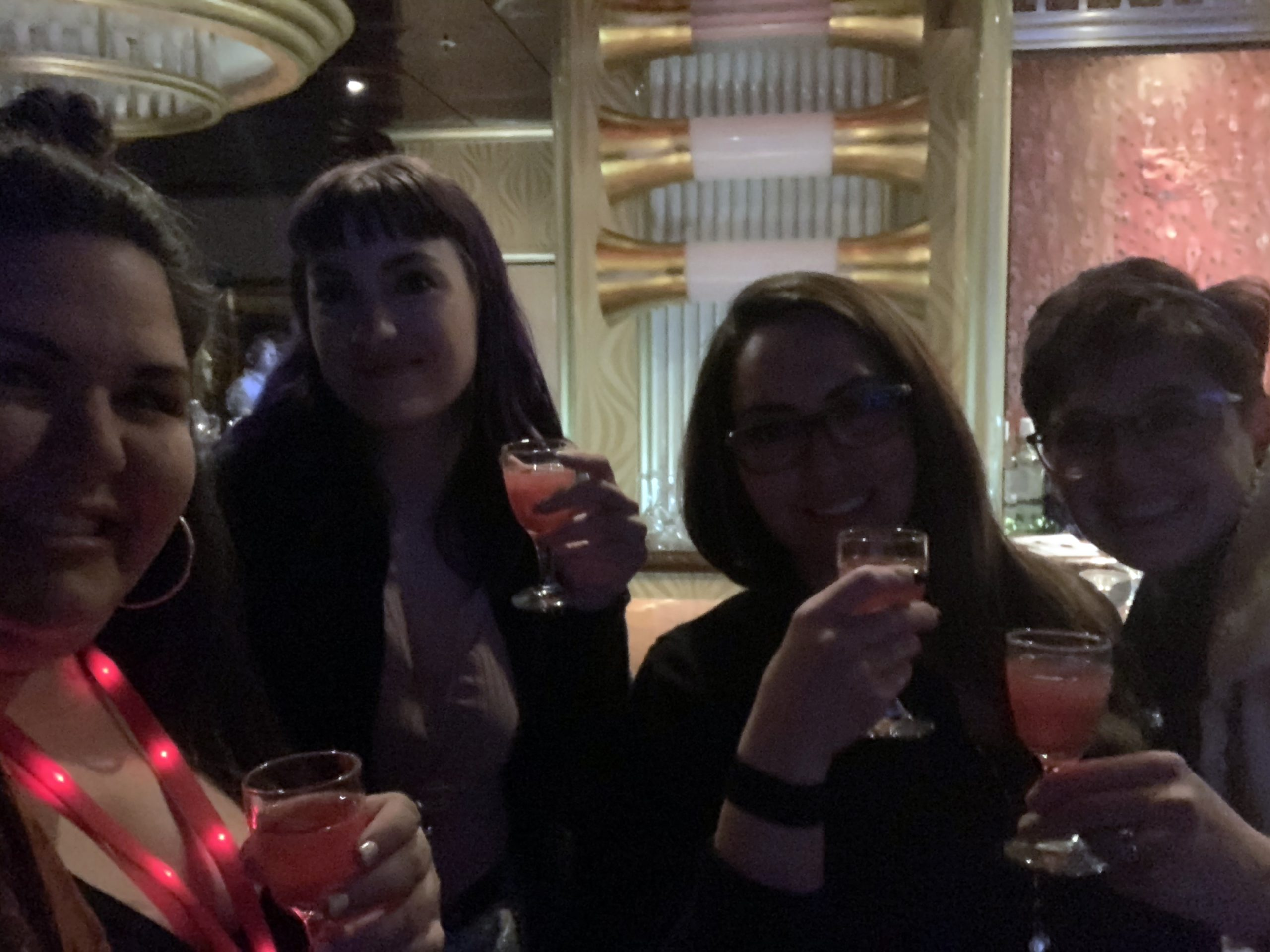 Four sisters smiling and about to have a shot together at the comedy show aboard Carnival Inspiration.