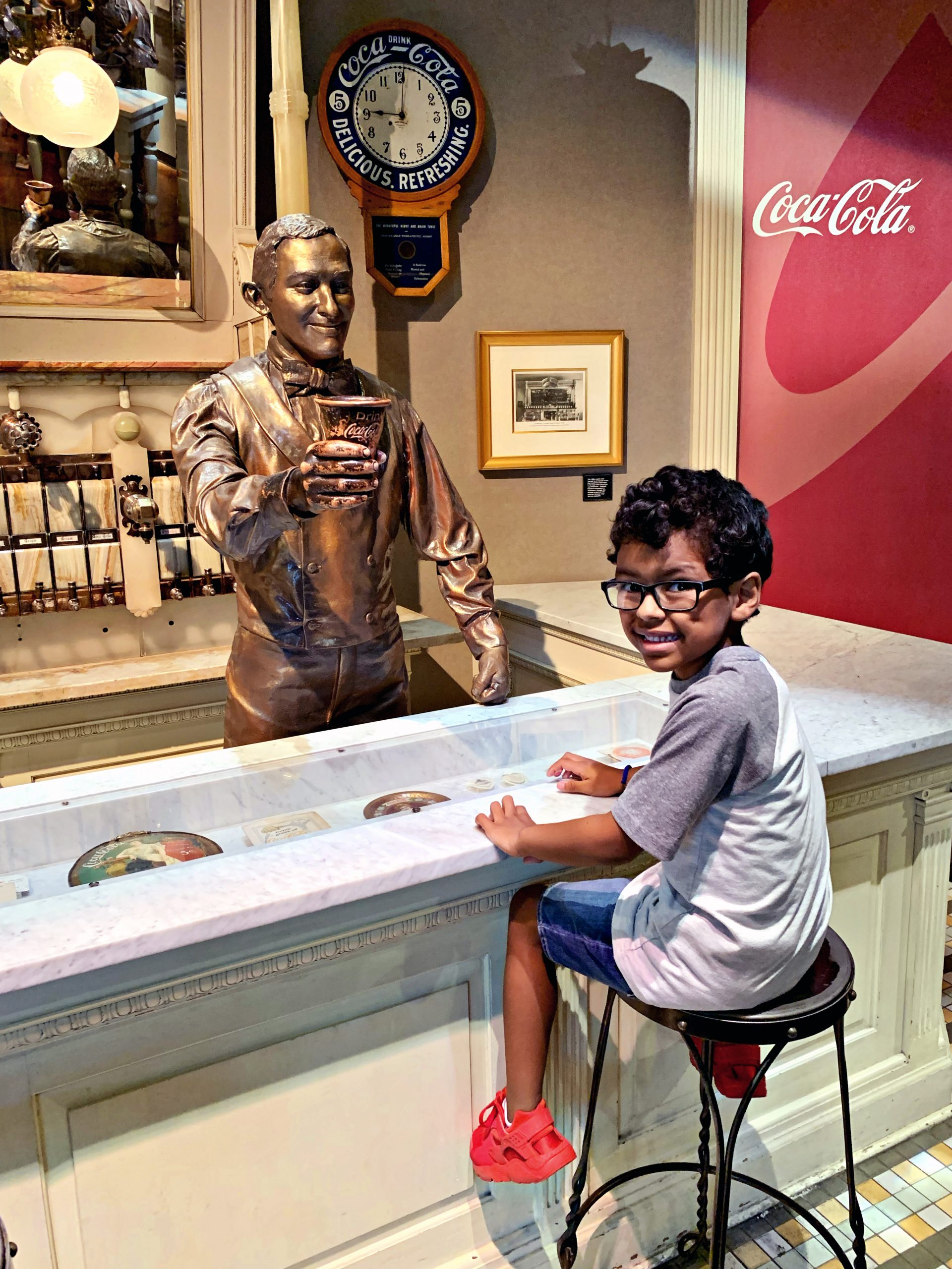 Boy smiling in front of a display at the World of Coca-Cola.