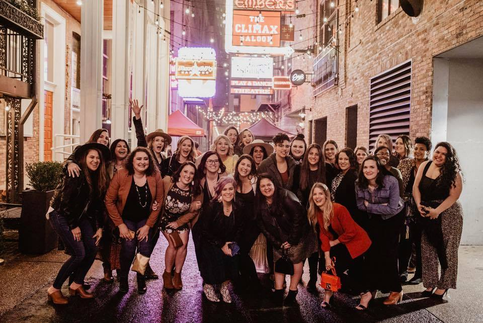 Group photo of 30 bloggers spending the weekend together in Nashville, TN. The photo is taken in the world famous Printer's Alley, by Ellie Kay Photography.
