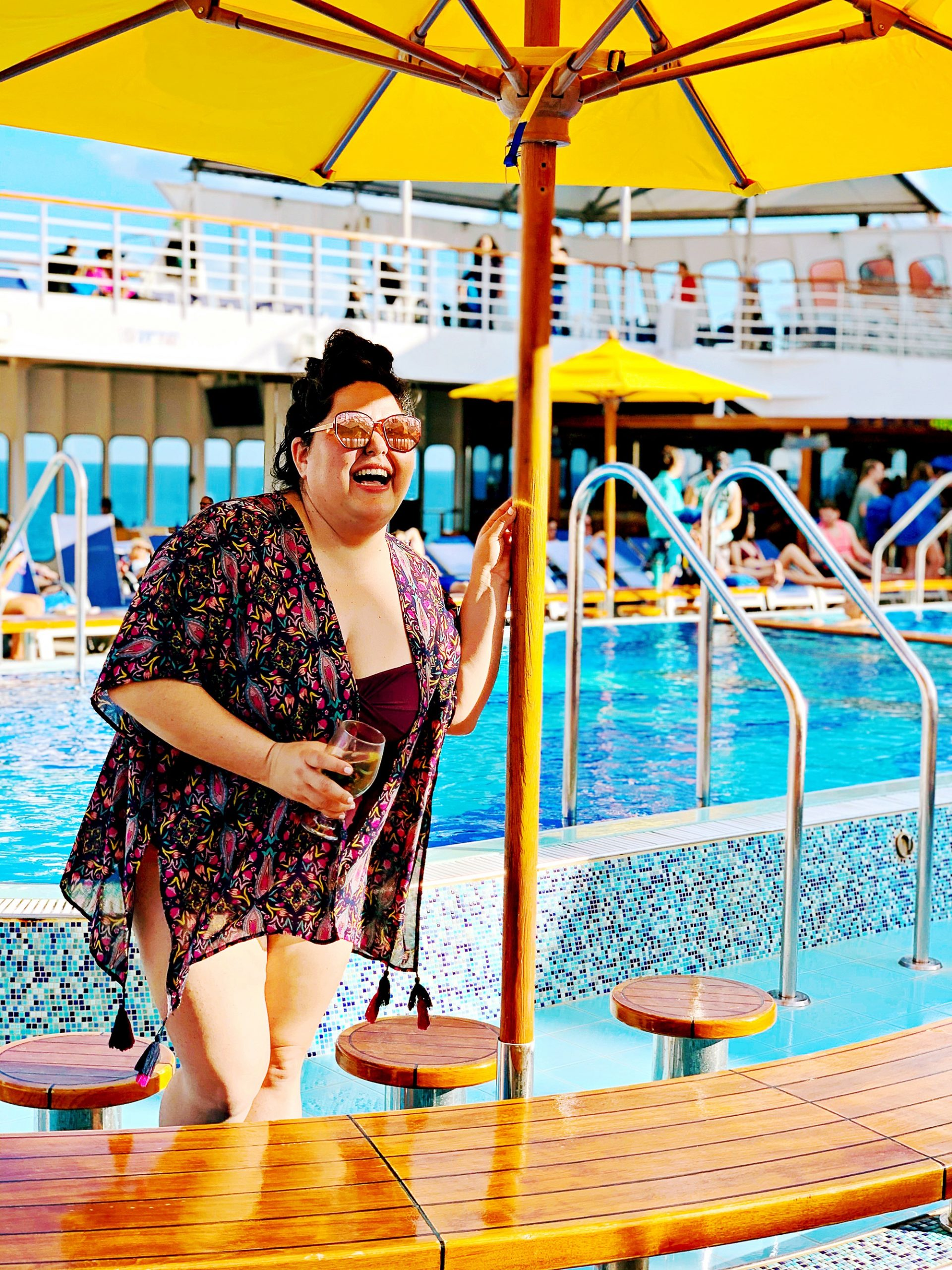 Woman laughing with one hand holding champagne and another resting on a pool umbrella, located on Lido deck of Carnival Paradise.