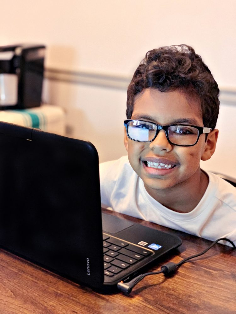 Photo of a smiling boy working on his Chrome Book laptop.