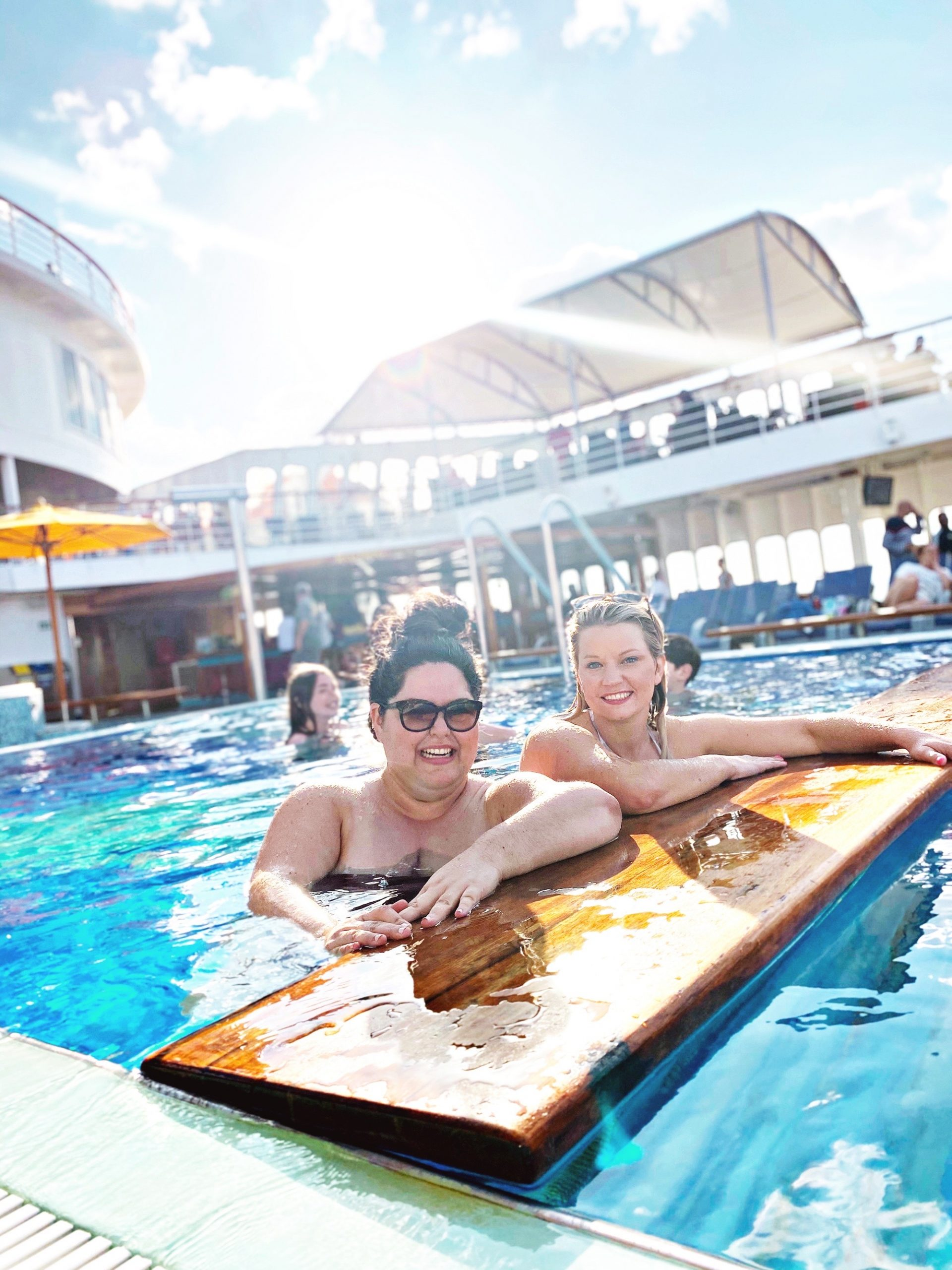 Two women smiling in the pool on a Carnival Paradise cruise.
