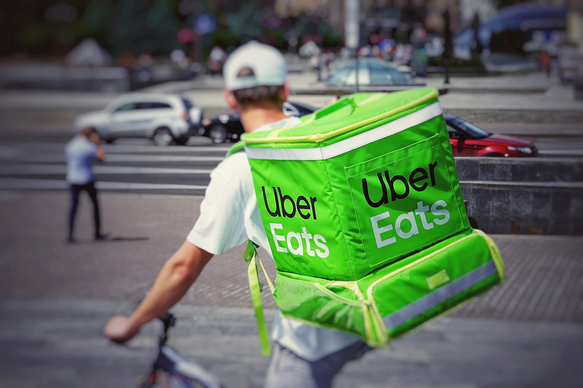 A man riding a bike with an Uber Eats cooler on his back.