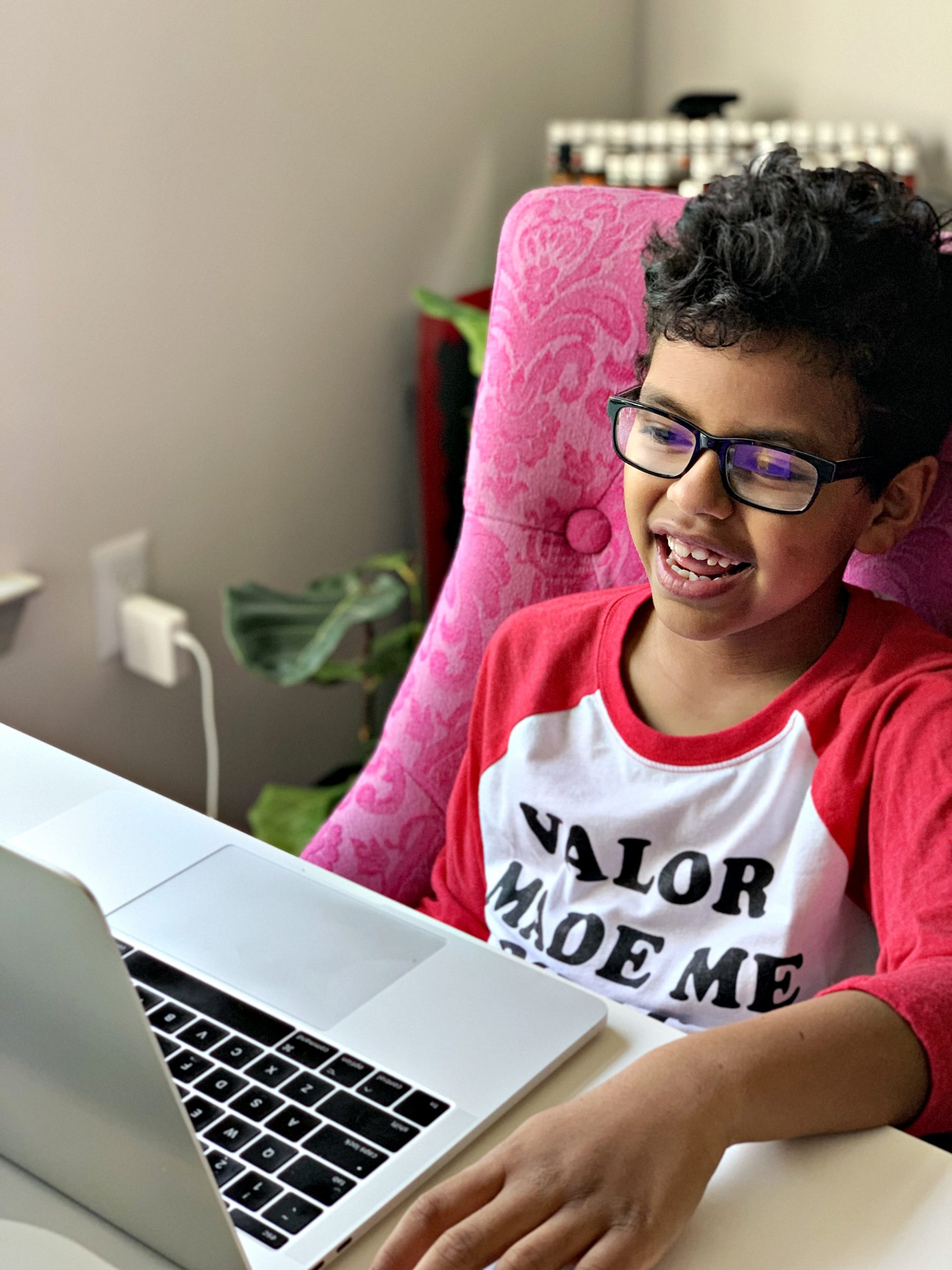 A smiling boy with glasses looking at an exciting digital learning program on a laptop.
