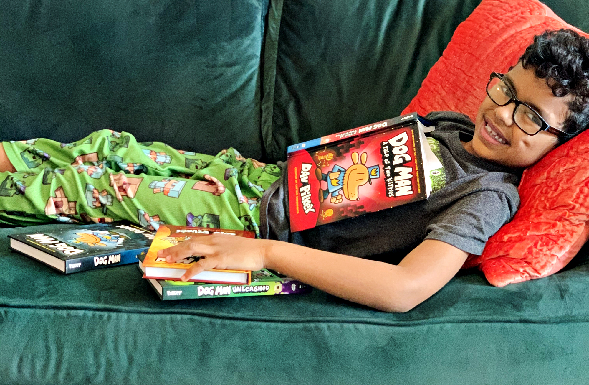 A boy smiling with a Dog Man book on his chest and his hand resting on three other books from the Dav Pilkey series.