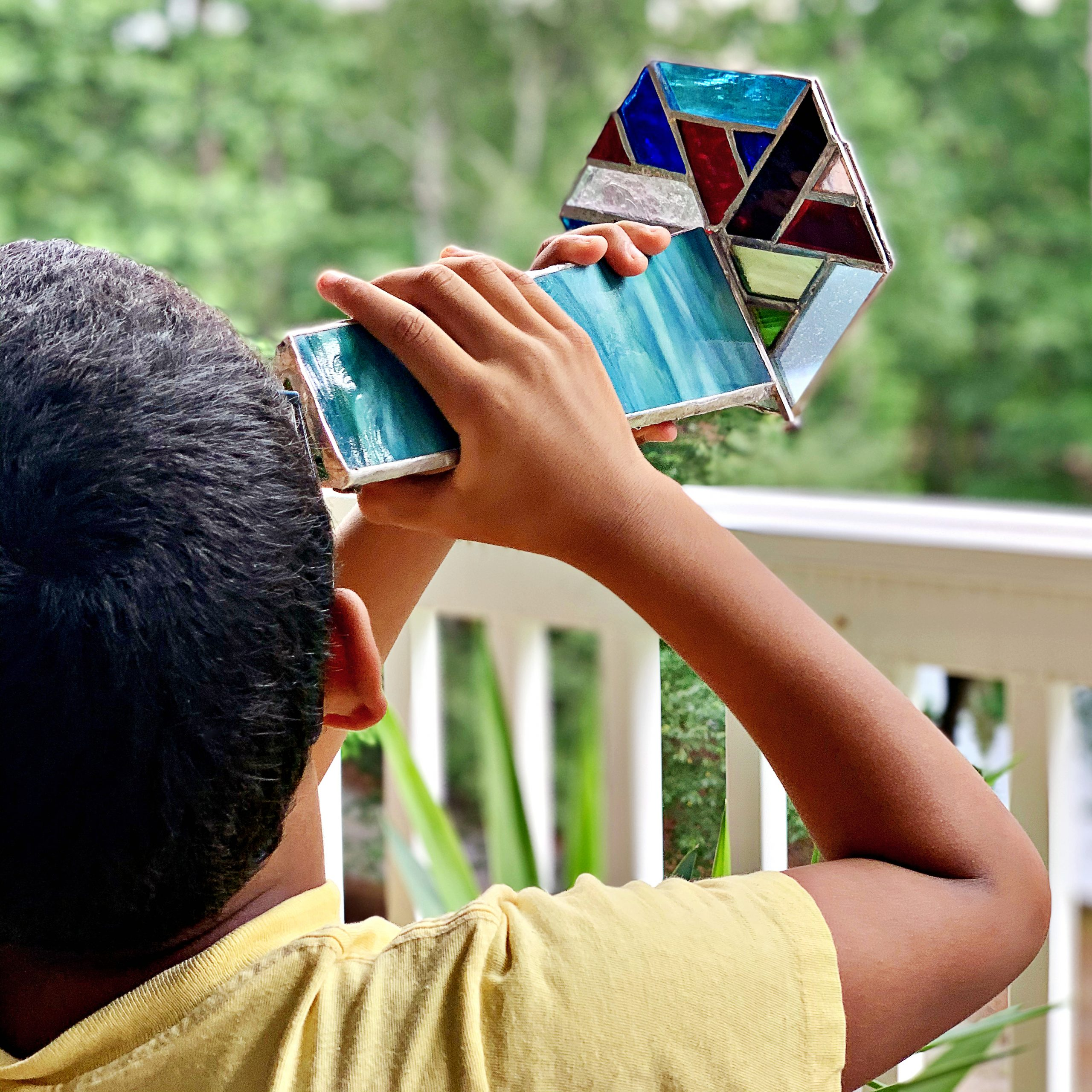 A boy looking through a handmade kaleidoscope, toward the trees.