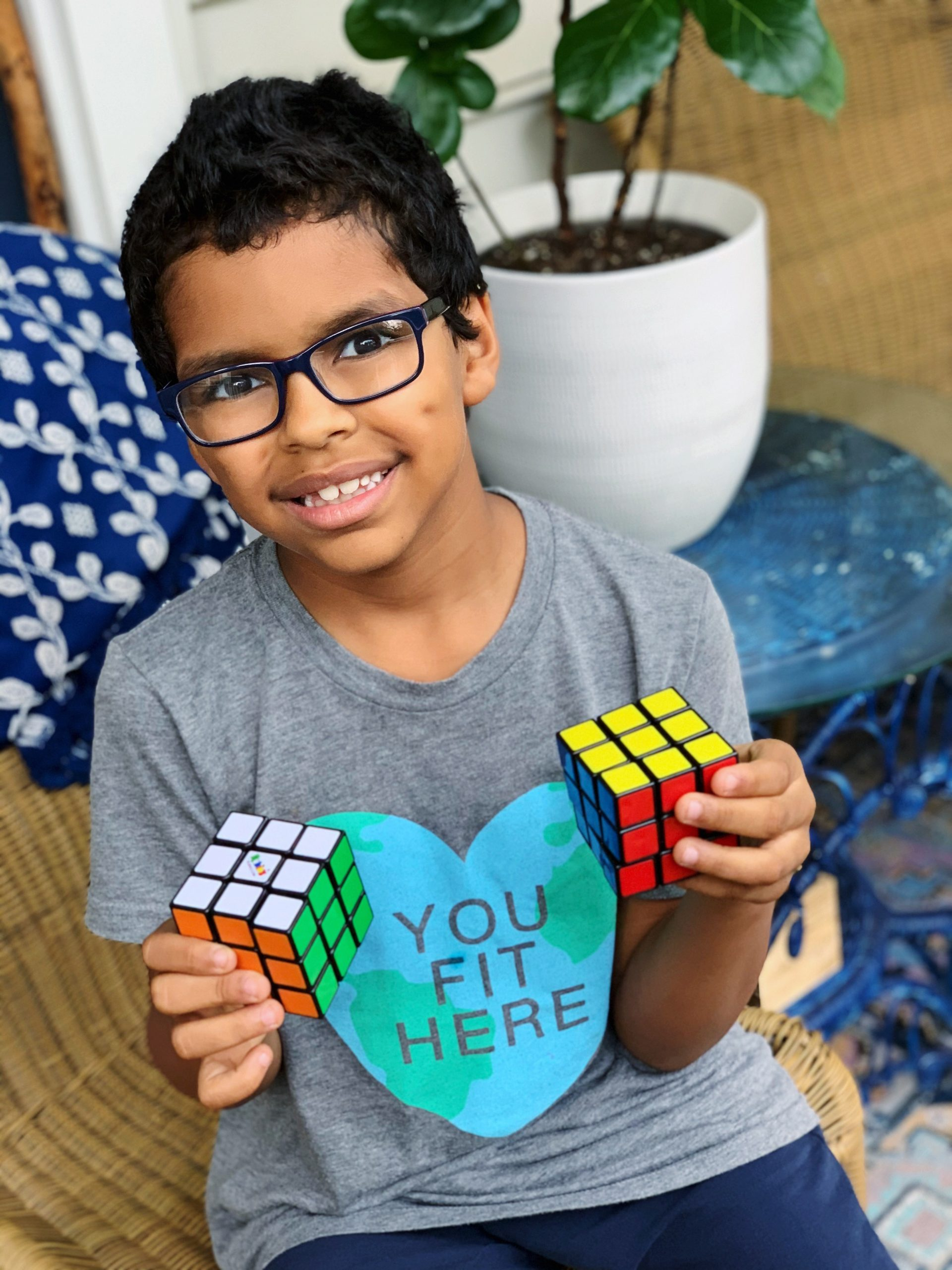 A smiling boy holding his first two solved 3x3 Rubik's cubes.