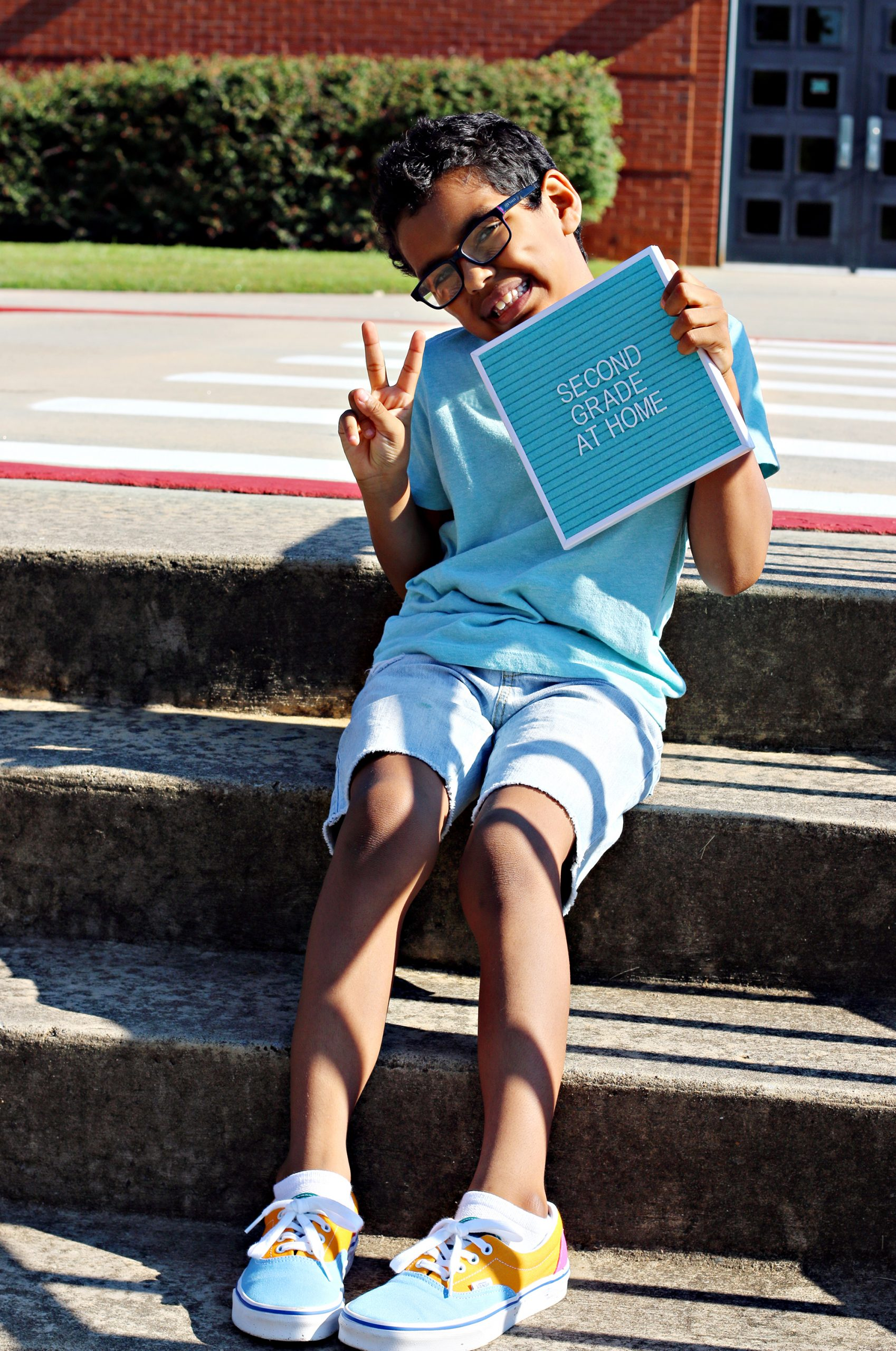 "A smiling boy sitting on the steps of his elementary school on the first day of second grade, holding up a peace sign and small letter board that says ""second grade at home""."